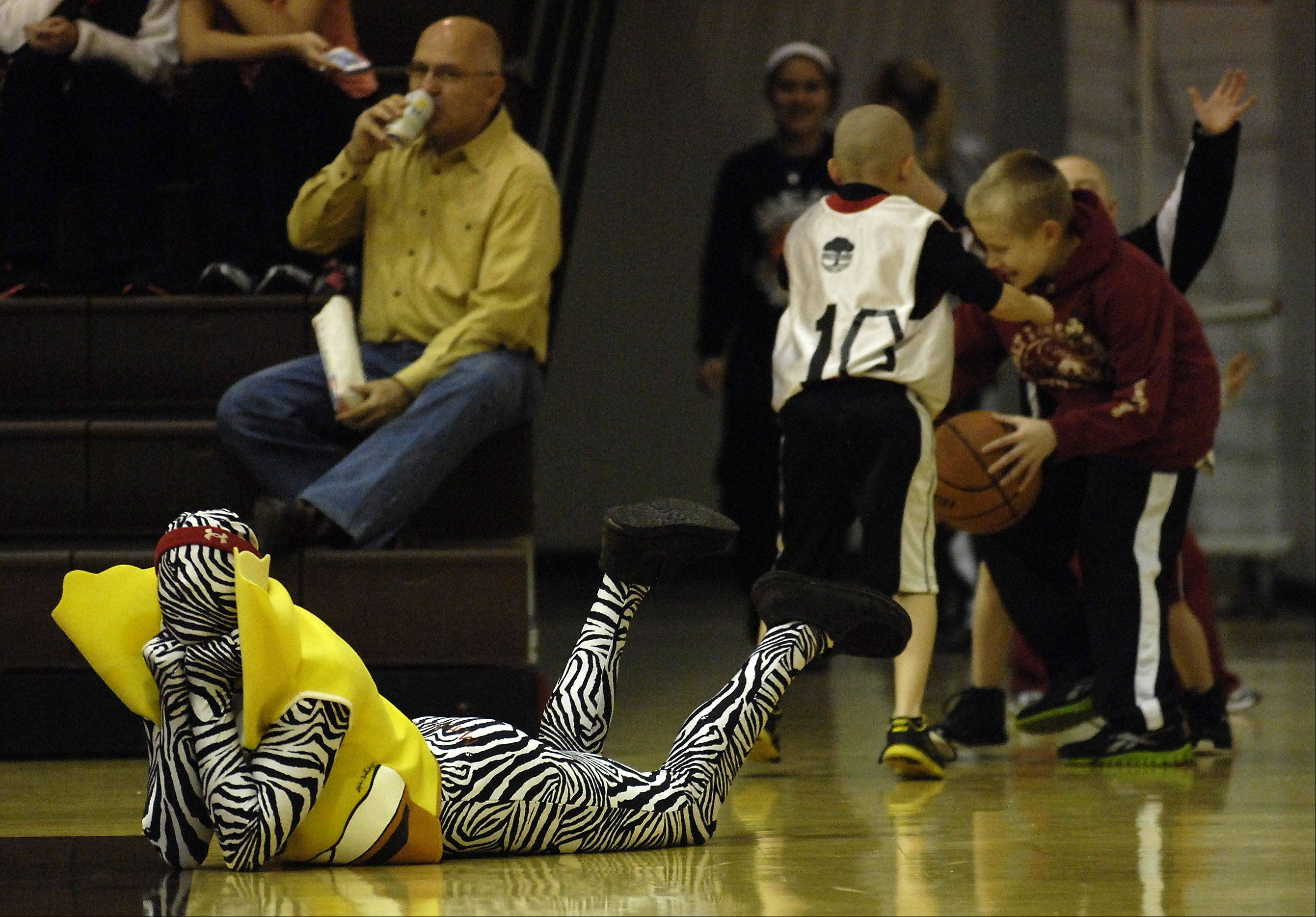 Huntley Red Raiders fan Nick Corpolongro, 18, of Huntley lays on the court before the championship of the Jacobs Holiday Tournament between Huntley and Crystal Lake Central.
