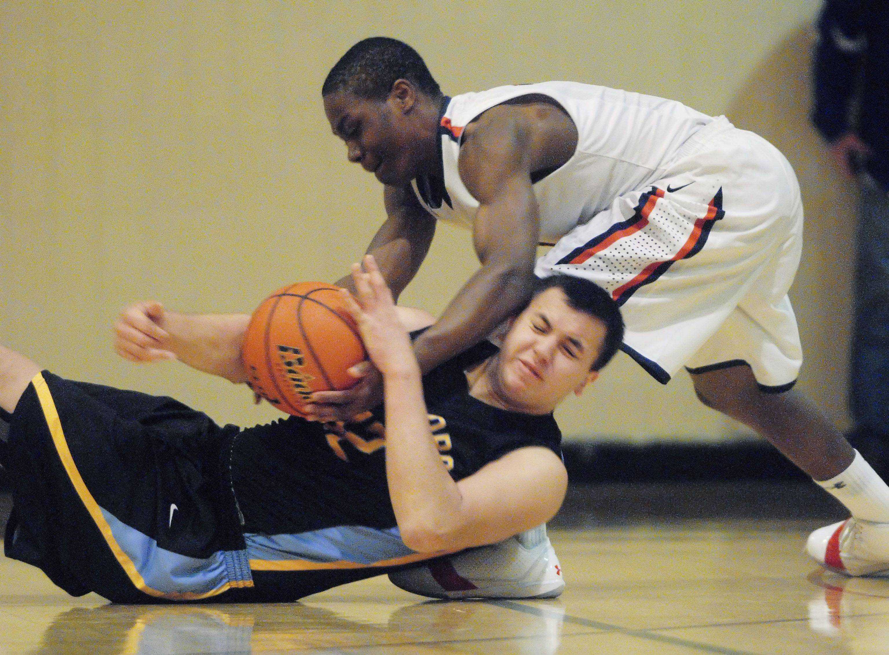 St. Viator's Mayo Arogundade takes the ball from Maine West's Matt Solis as he falls to the floor during Tuesday night's game at Wheeling.