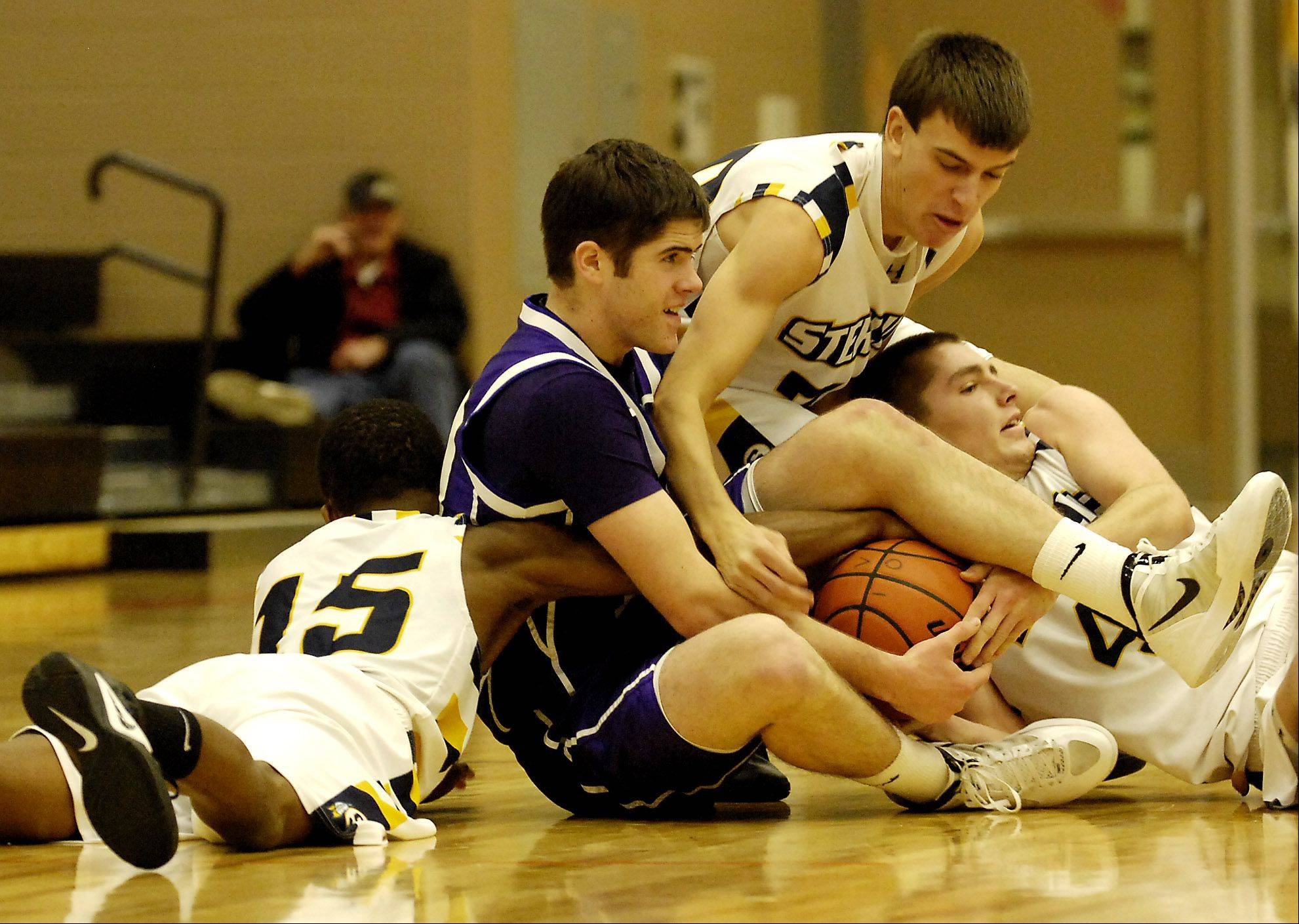 Hampshire's Tyler Crater battles Sterling's Cornell Hartz (left), Nathan Blackburn (middle), and Patrick Petrosky (right), for a loose ball during their game Wednesday in Dekalb.
