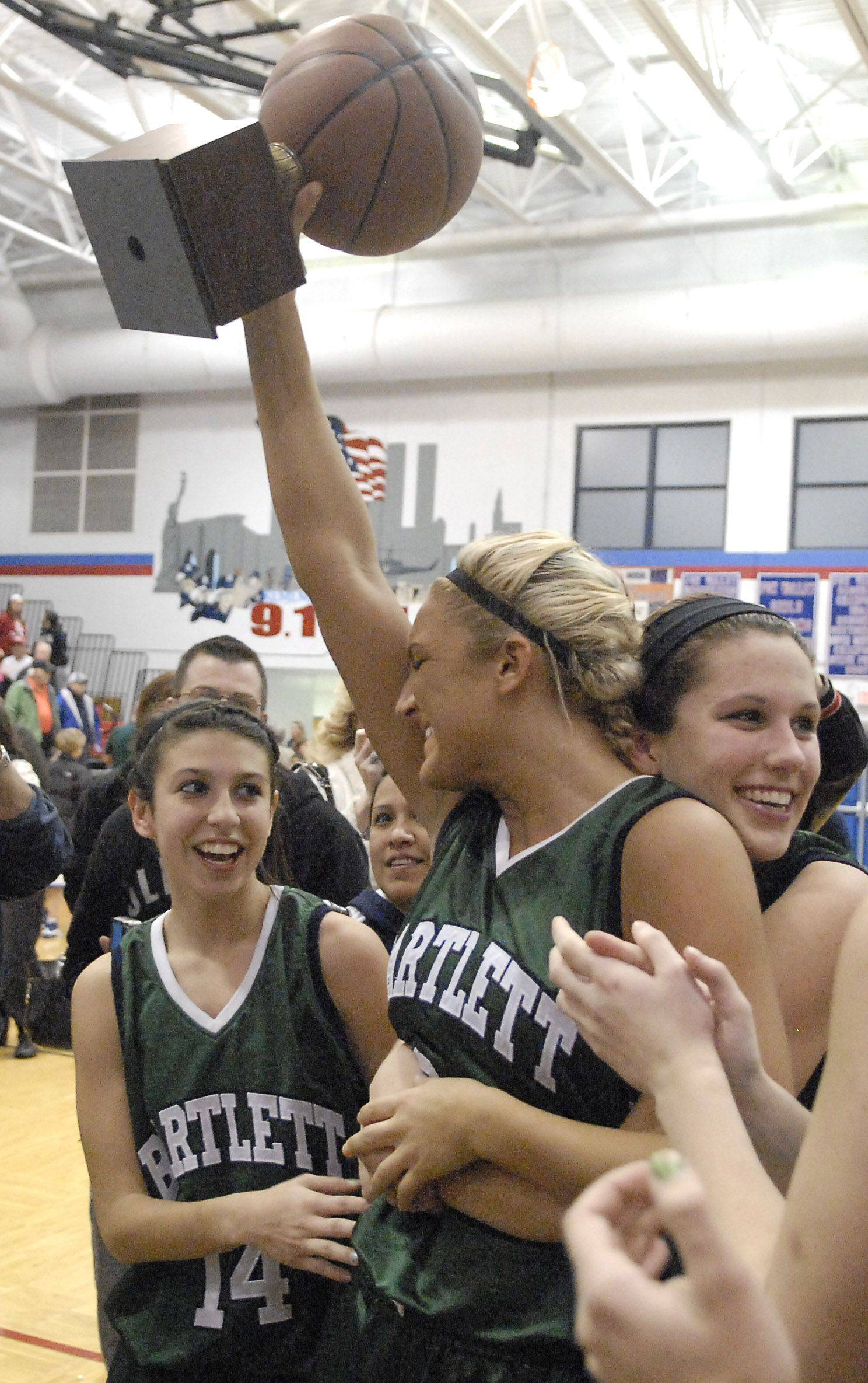 Bartlett's Haley Videckis hoists the trophy for the Hawks after winning the championship game over New Trier at Dundee-Crown's tournament on Thursday, December 29.