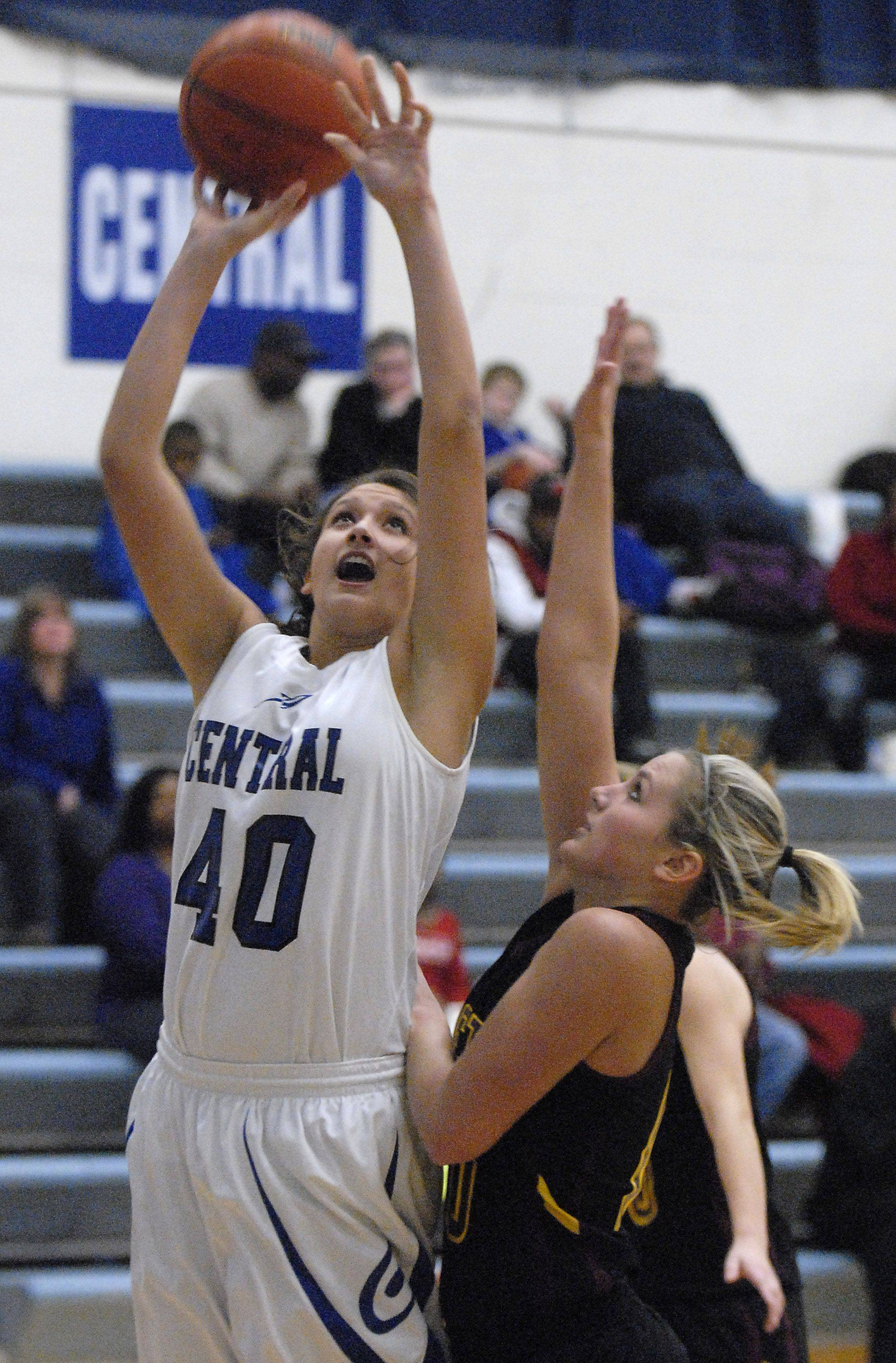 Burlington Central's Alison Colby shoots past an attempted block by Richmond-Burton's Alex Callanan in the first quarter on Saturday at Central.