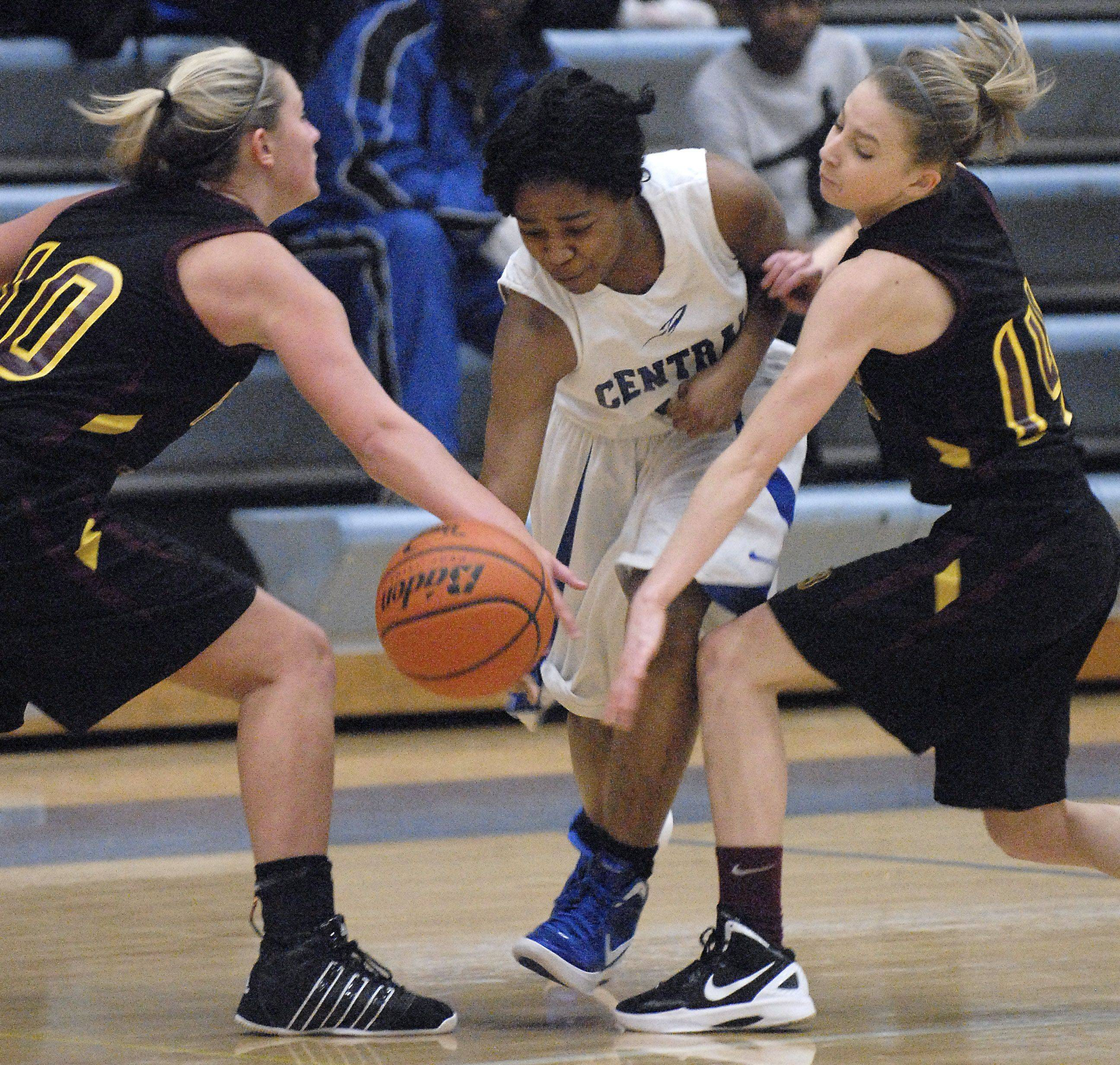 Burlington Central's Erica Haynes busts through a block by Richmond-Burton's Alex Callanan, left, and Erin Thomas in the first quarter on Saturday, January 14.