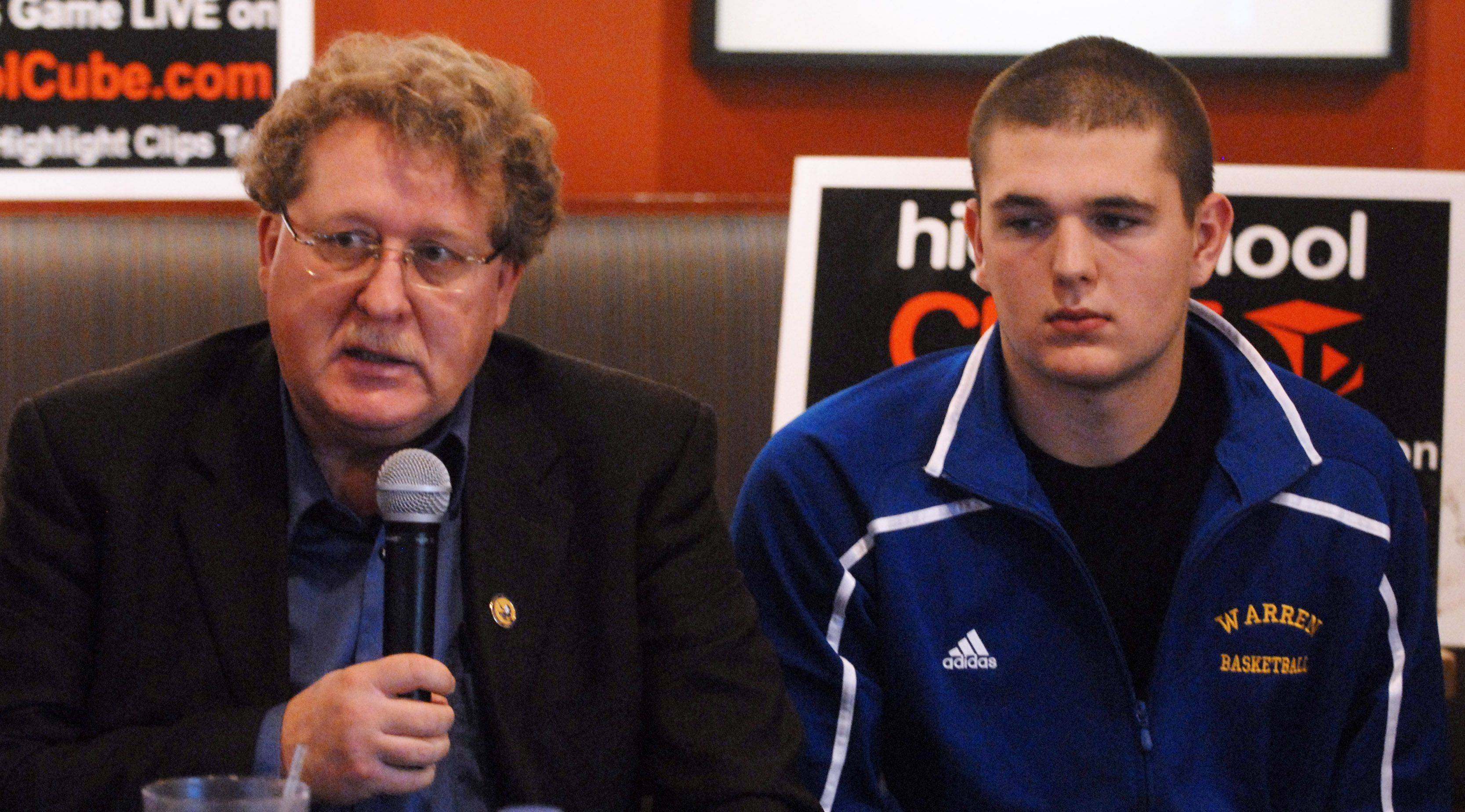 Warren boys basketball coach Chuck Ramsey, seated with the Blue Devils' Nathan Boothe, speaks during a Hoops Showdown press conference at Lou Malnati's in Schaumburg Tuesday.