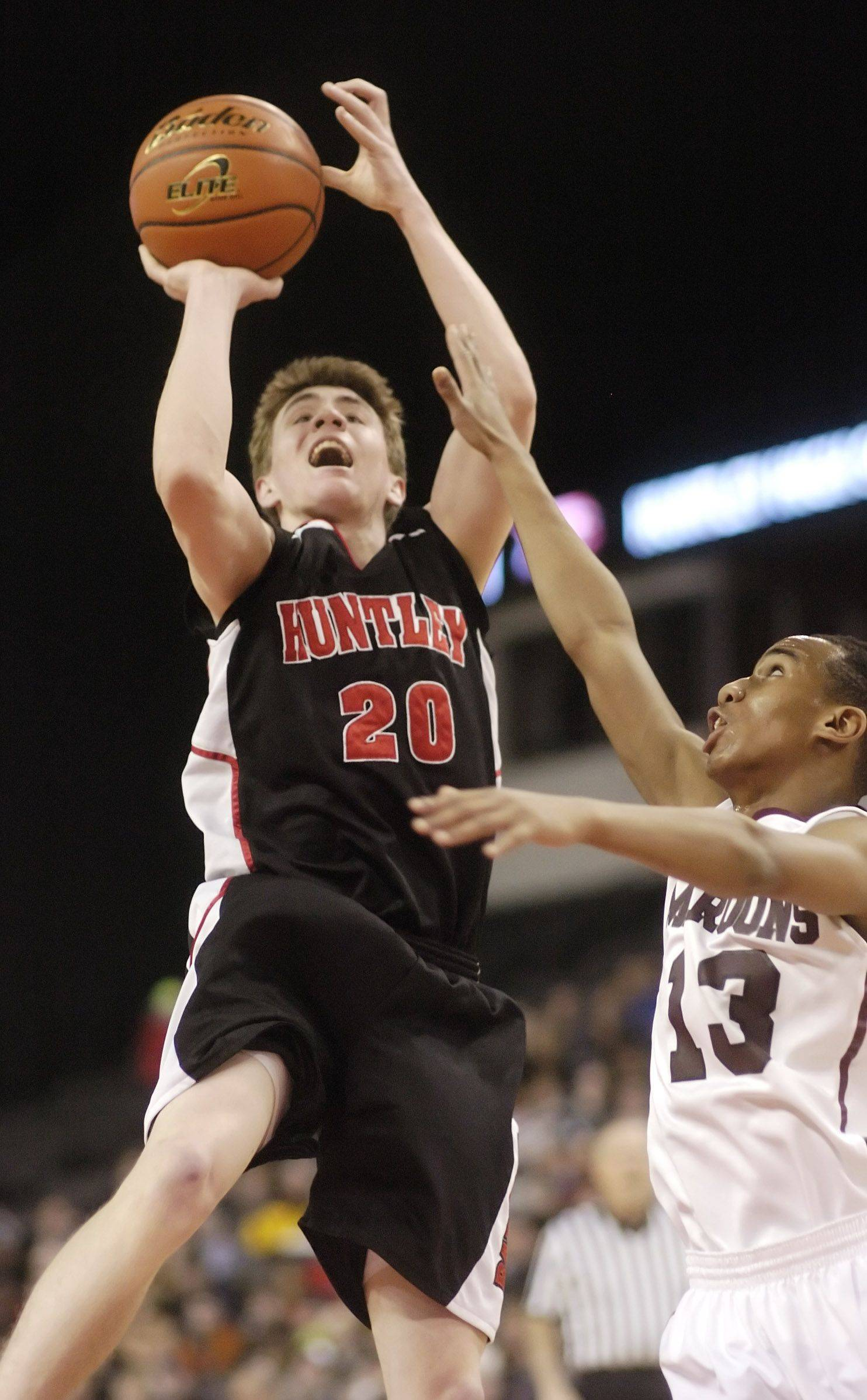 Huntley's Troy Miller, left, takes a shot against the defense of Elgin's Cortez Scott during Saturday's High School Hoops Showdown game at the Sears Centre in Hoffman Estates.