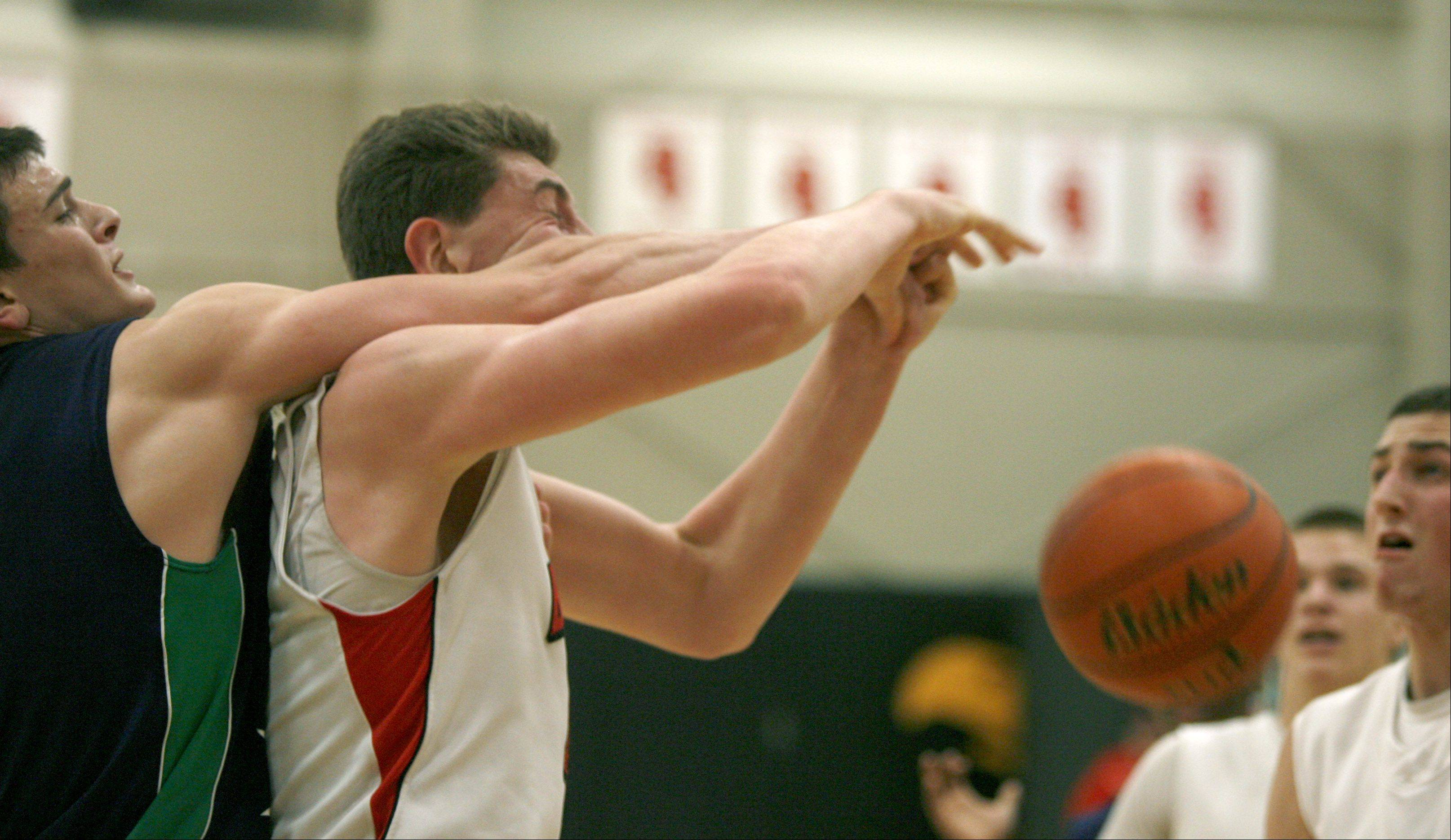 Benet Academy's Sean O'Mara, center, is fouled during boys basketball action against Notre Dame.