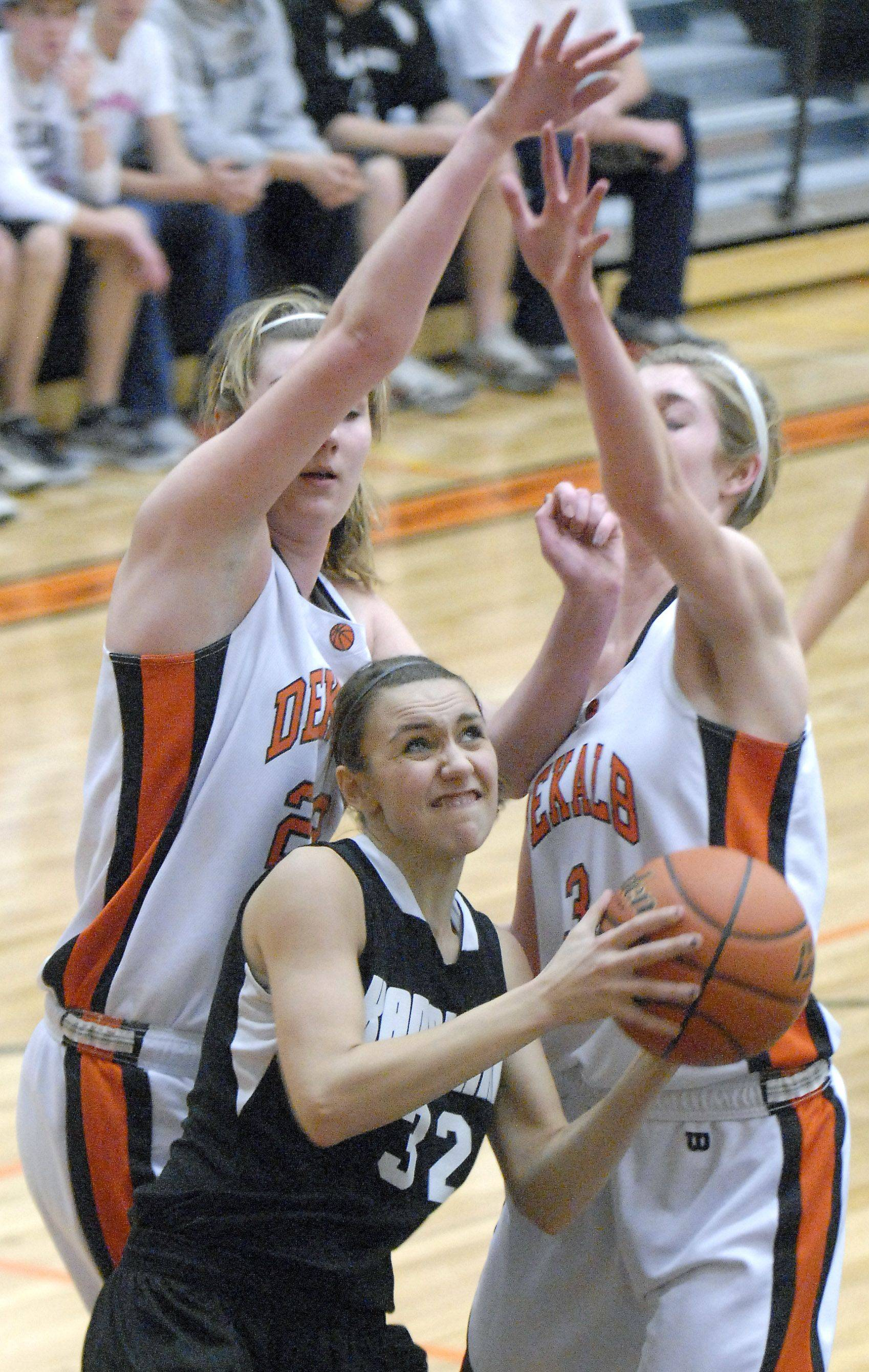 Laura Stoecker/lstoecker@dailyherald.comKaneland's Emma Bradford shoots past a block by DeKalb's Emily Bemis and Courtney Bemis in the first quarter on Tuesday, January 31.