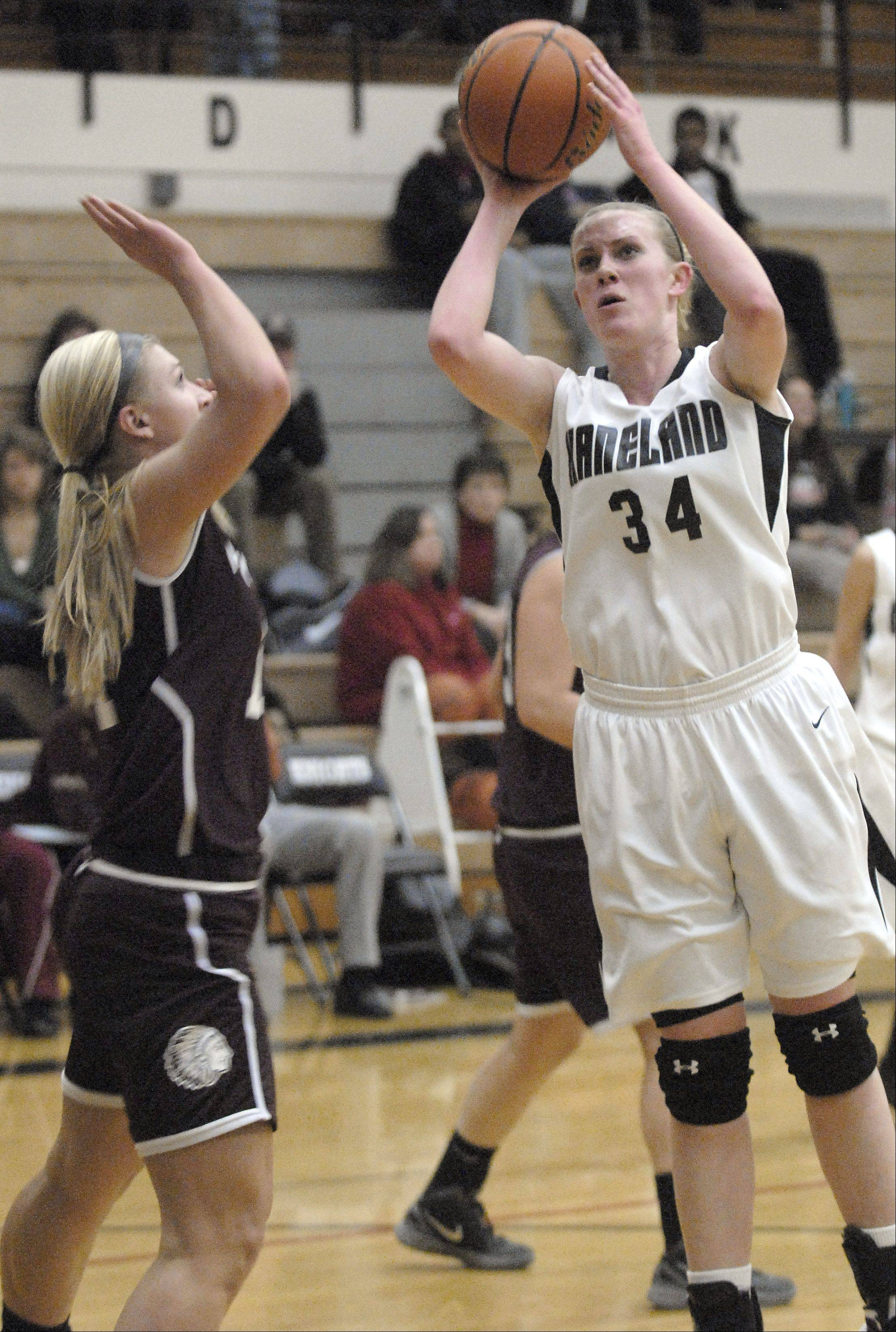 Marengo's Allison Rogutich attempts to block a shot by Kaneland's Kelly Evers in the first quarter on Tuesday, February 7.