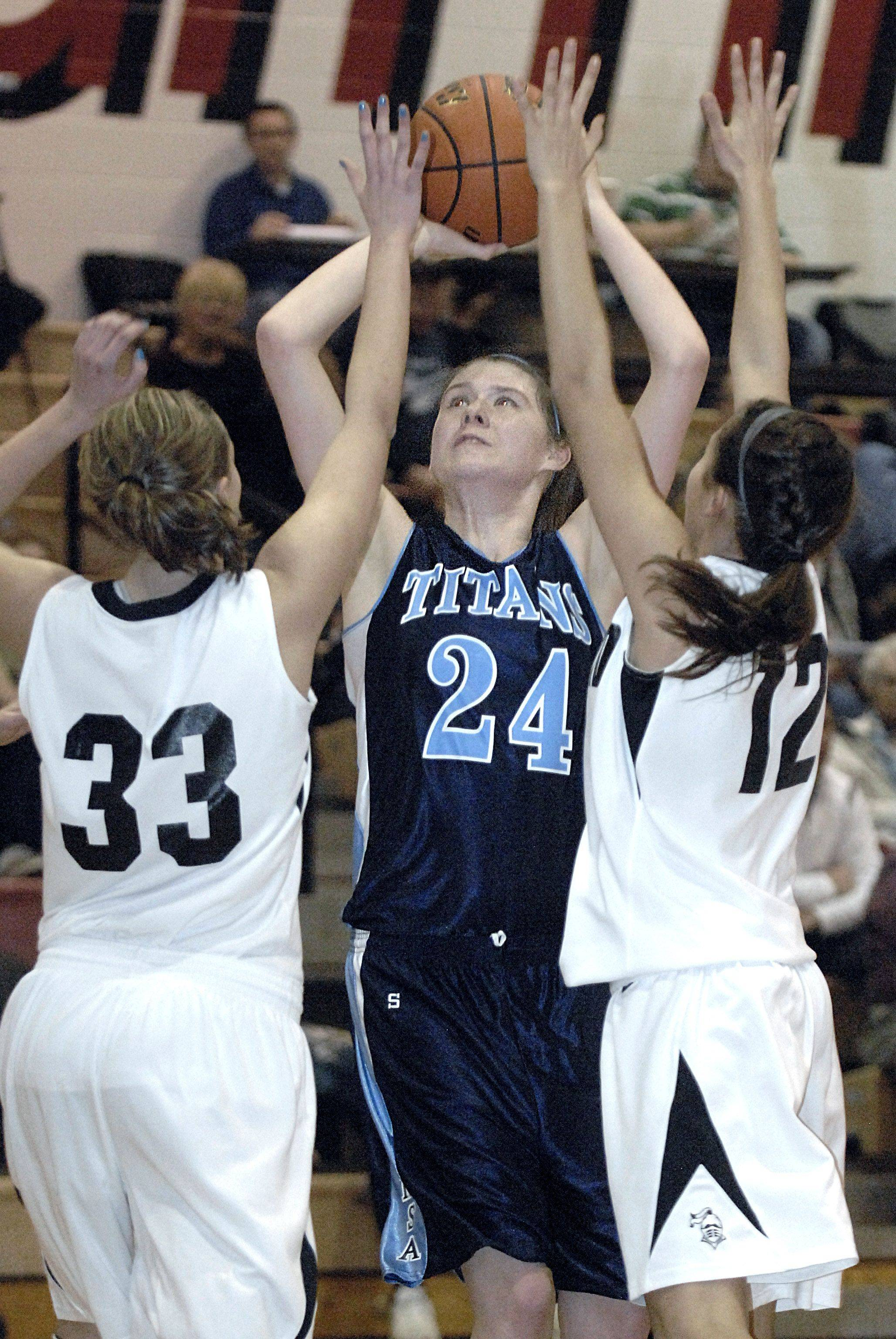 IMSA's Lindsey Conley is swarmed by Kaneland's Marina Schaefer, left, and Ashley Castellanos in the third quarter of regional game on Wednesday, February 15.
