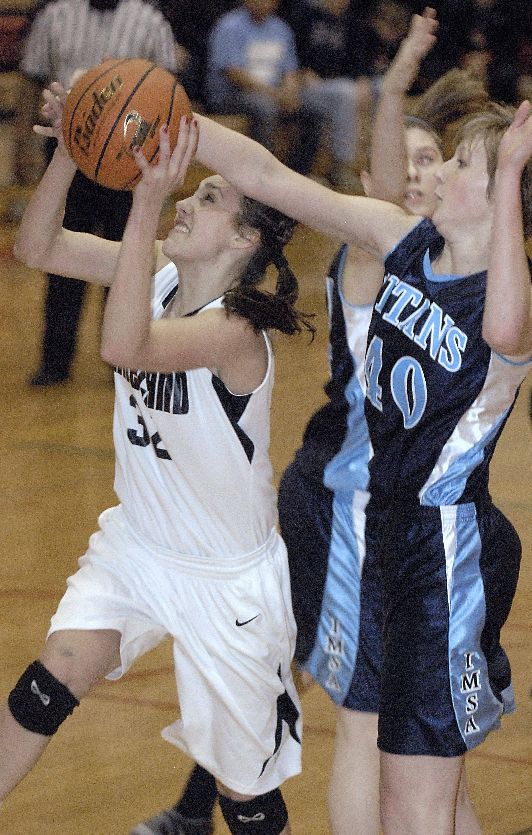 IMSA's Michaela Edgers blocks a shot by Kaneland's Emma Bradford in the second quarter of regional game on Wednesday, February 15.