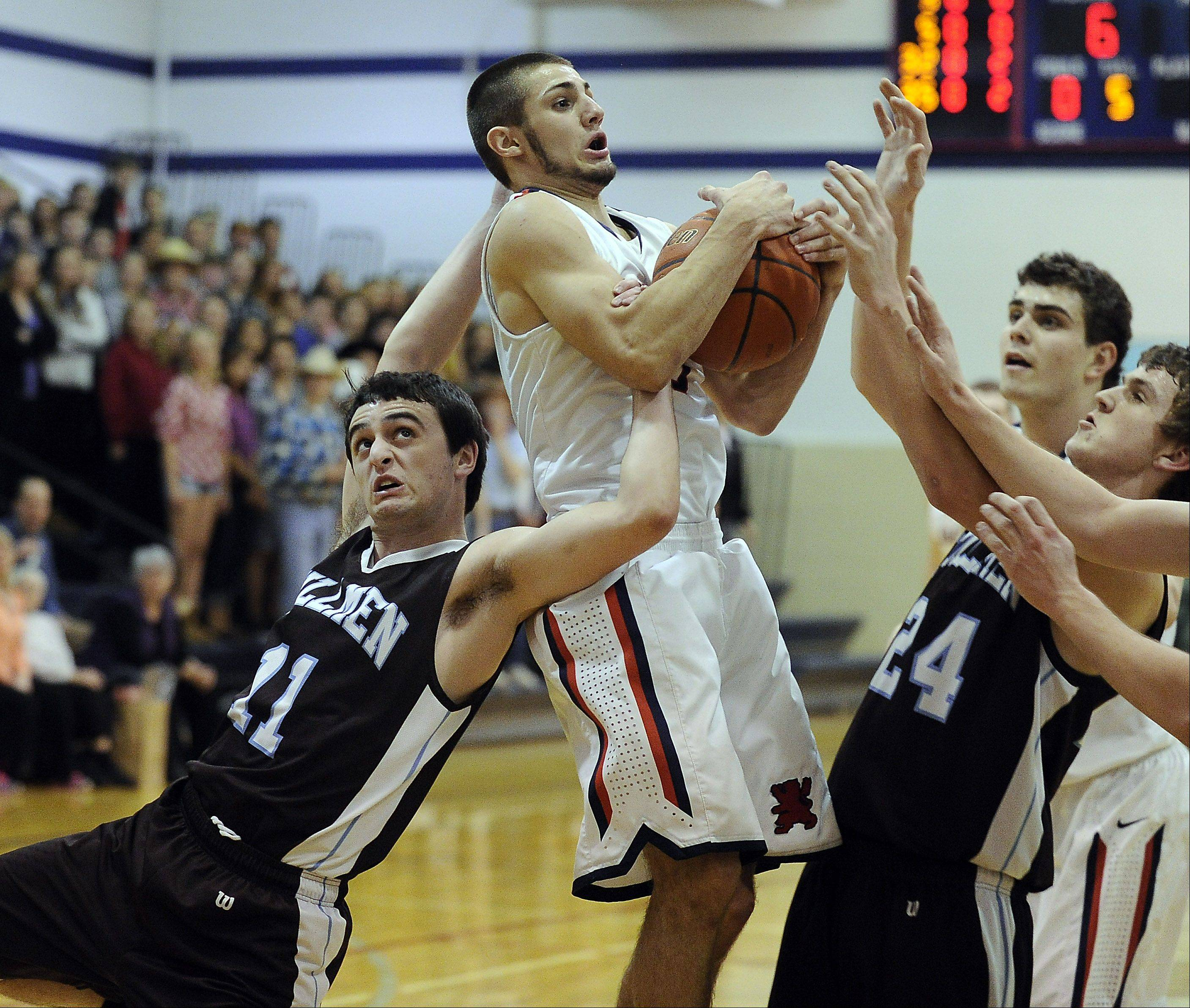 St. Viator's DJ Morris battles with Joliet Catholic's James Ragen for control of the ball Thursday at St. Viator.