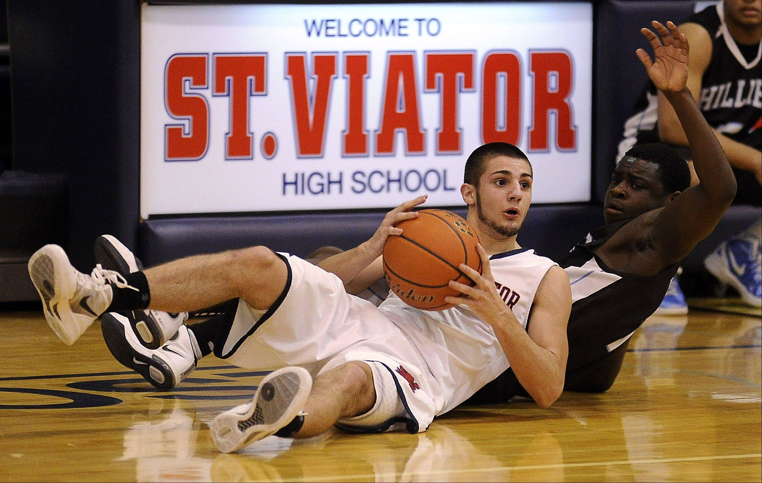 St. Viator's DJ Morris battles with Joliet Catholic Academy's Brandon Smith for control of a loose ball in the first half.