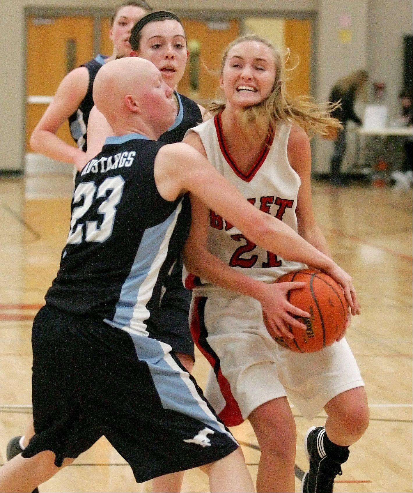 Sidney Prasse of Benet Academy, right, tries to hang onto the ball as Sarah Ludwig of Downers Grove South tries to knock it away in girls basketball action Tuesday in Lisle.