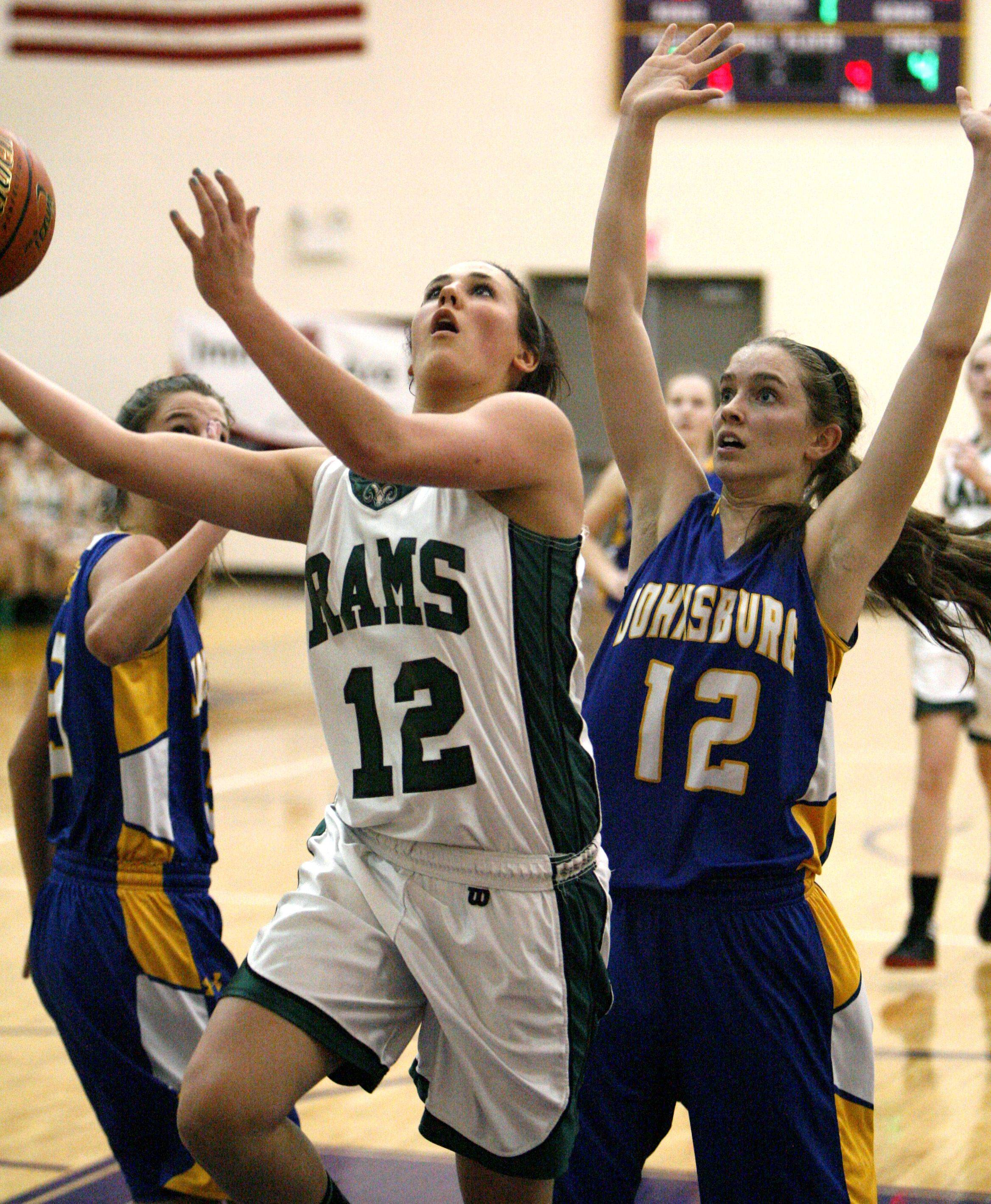Grayslake Central's Claire Brennan drives the lane past Johnsburg defender Stephanie Cherwin for a layup in Class 3A regional final play Friday.