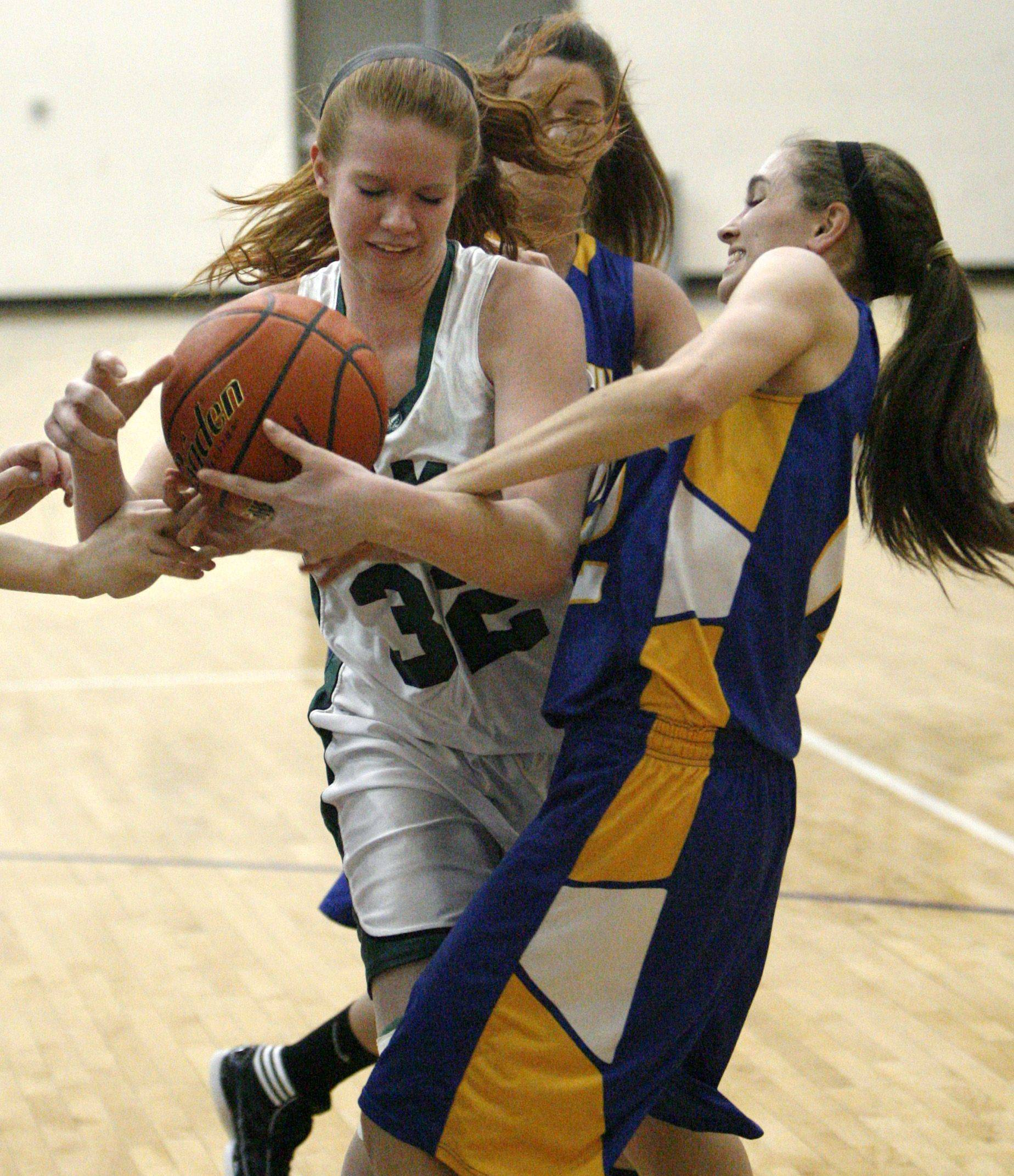 Grayslake Central's Morgan Dahlstrom pulls in an offensive rebound against Johnsburg defender Stephanie Cherwin in Class 3A regional final play Friday.