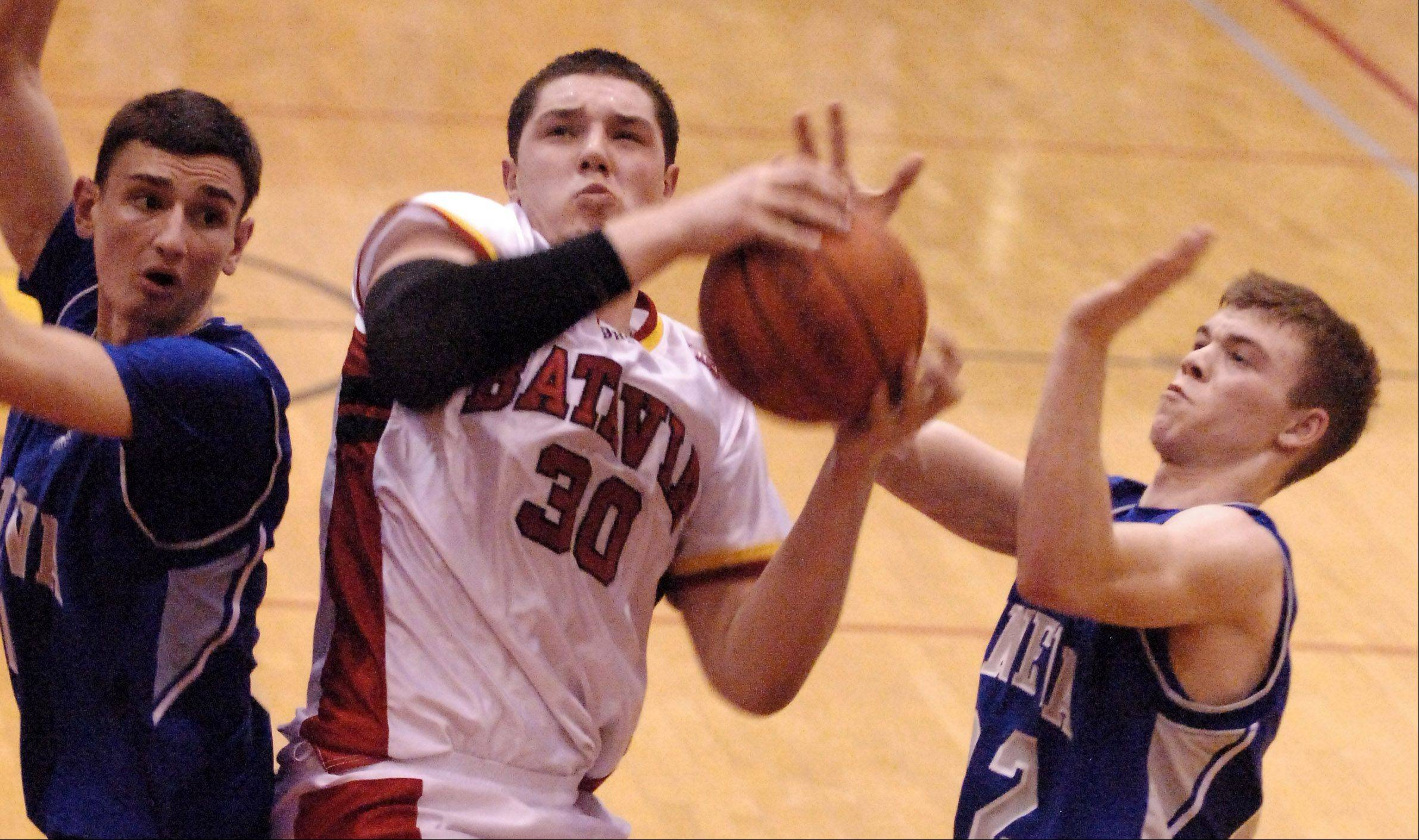 Batavia's Cole Gardner rips down an offensive rebound and is fouled while scoring.