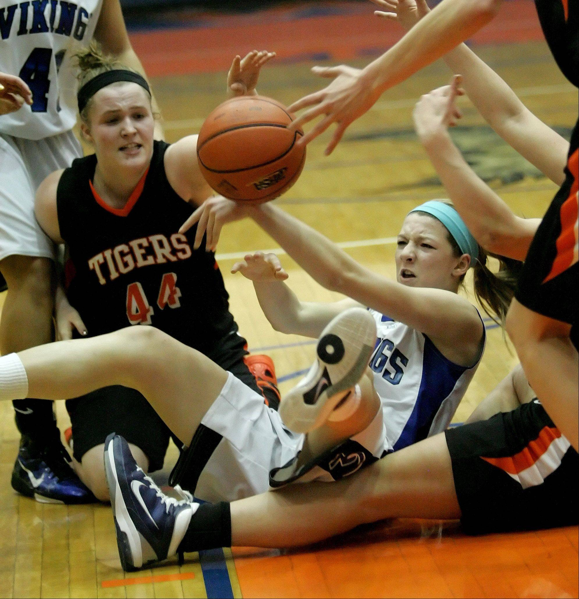 Olivia Linebarger of Wheaton Warrenville South, left , and Michaela Loebel of Geneva tumble chasing a ball.