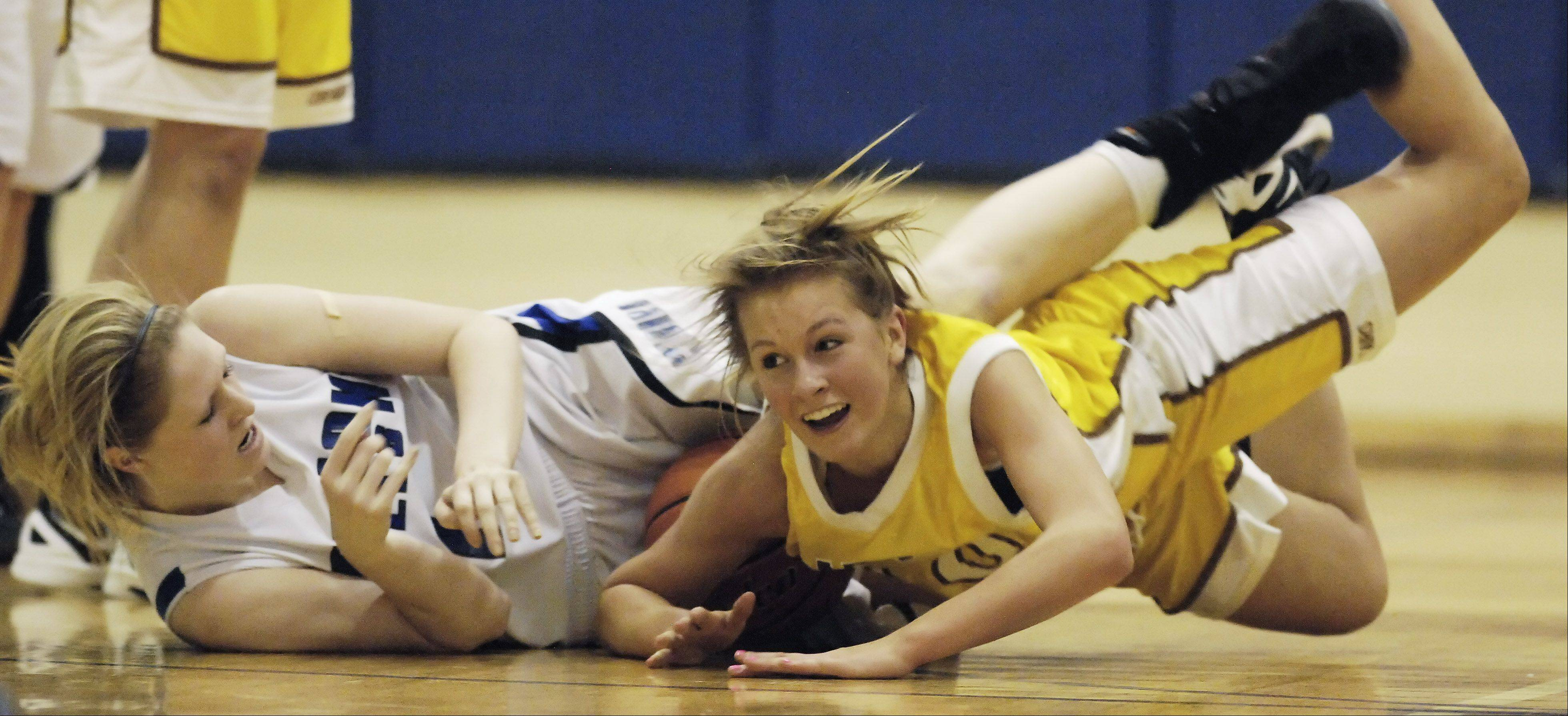 Sydney Smith, left, of Vernon Hills and Leah Lach of Carmel dive to the floor after the ball.