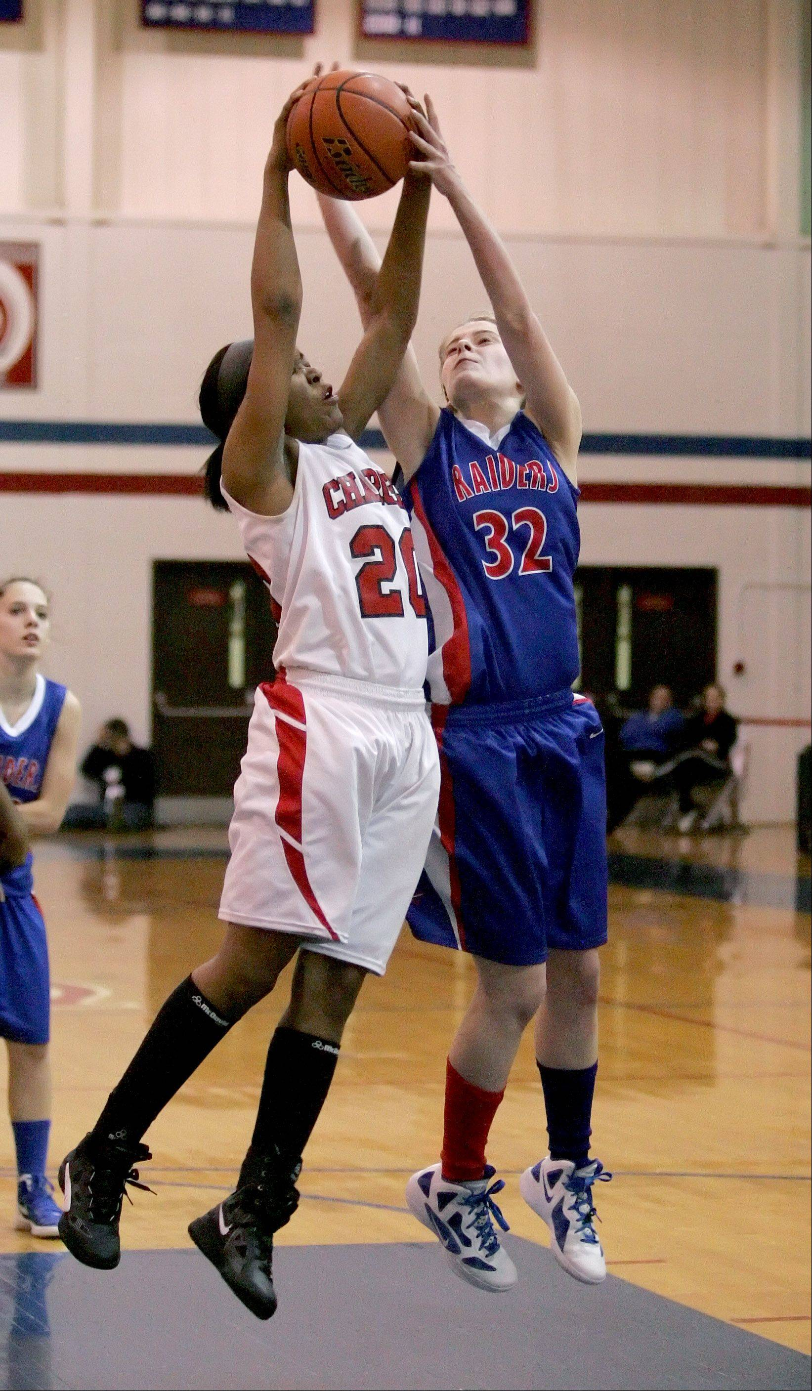 Tomei Ball, right, of Glenbard South and Briya Wilborn, left, of St. Joseph go up for a rebound .