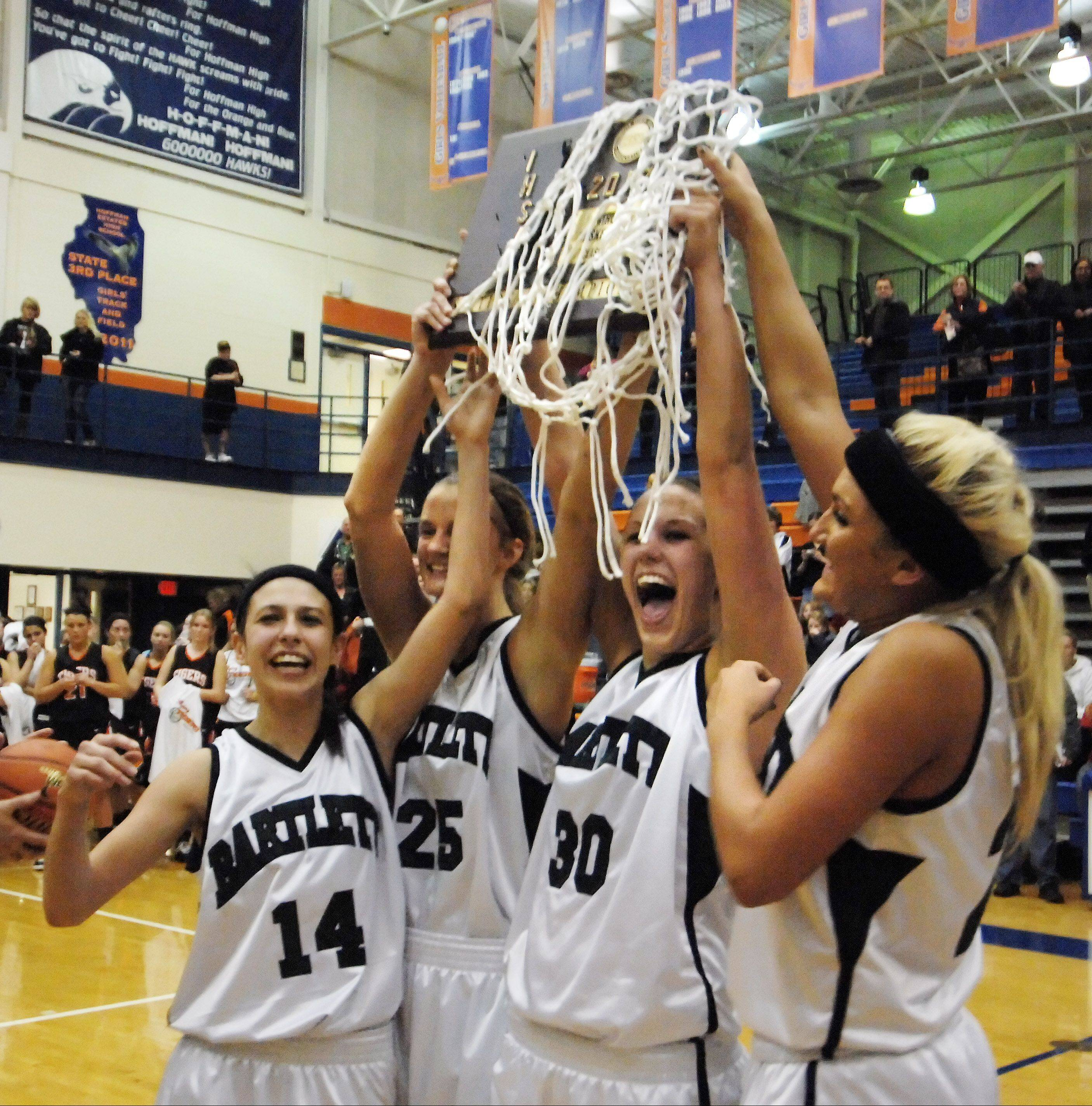 Bartlett's Janessa Baker, left, Kristin Conniff, Lisa Palmer and Haley Videckis, right, hold the trophy after defeating Wheaton Warrenville South 54-51 in overtime in Thursday's Class 4A Hoffman Estates sectional championship game.