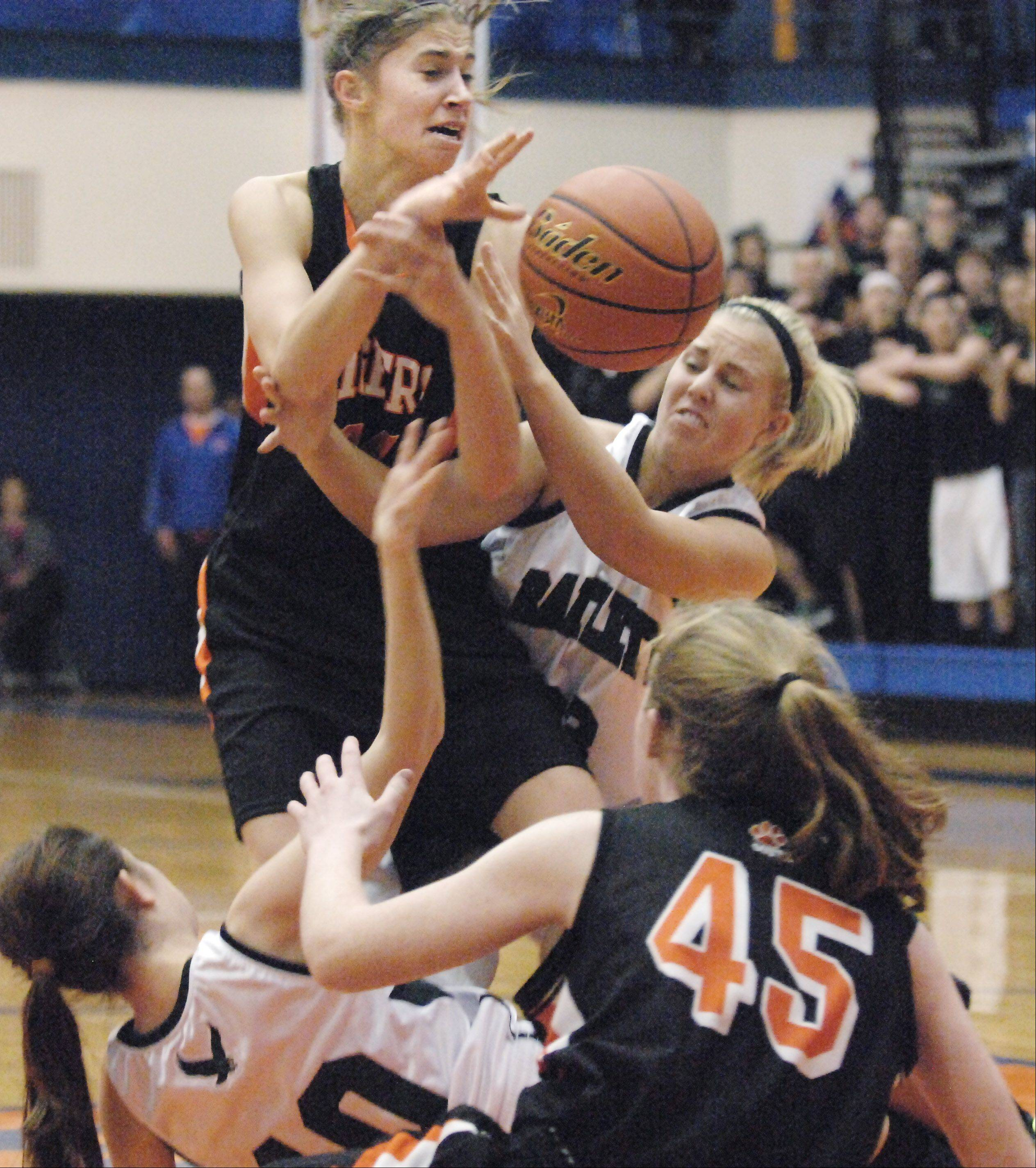 Bartlett's Ashley Johnson knocks the ball form Wheaton Warrenville South's Kasey Gassensmith .