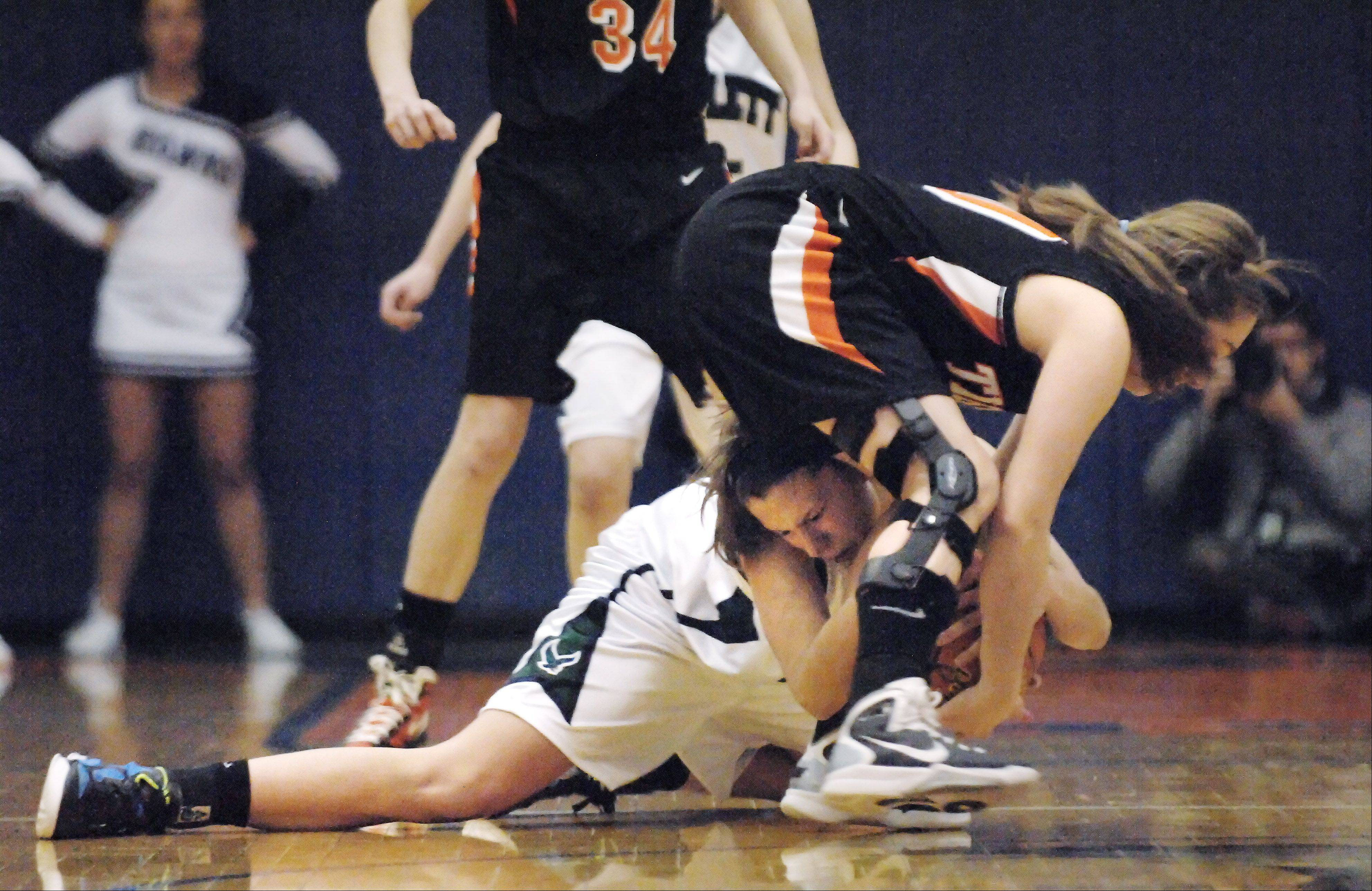 Bartlett's Lisa Palmer grabs a loose ball and the leg of Wheaton Warrenville South's Sierra Bisso.