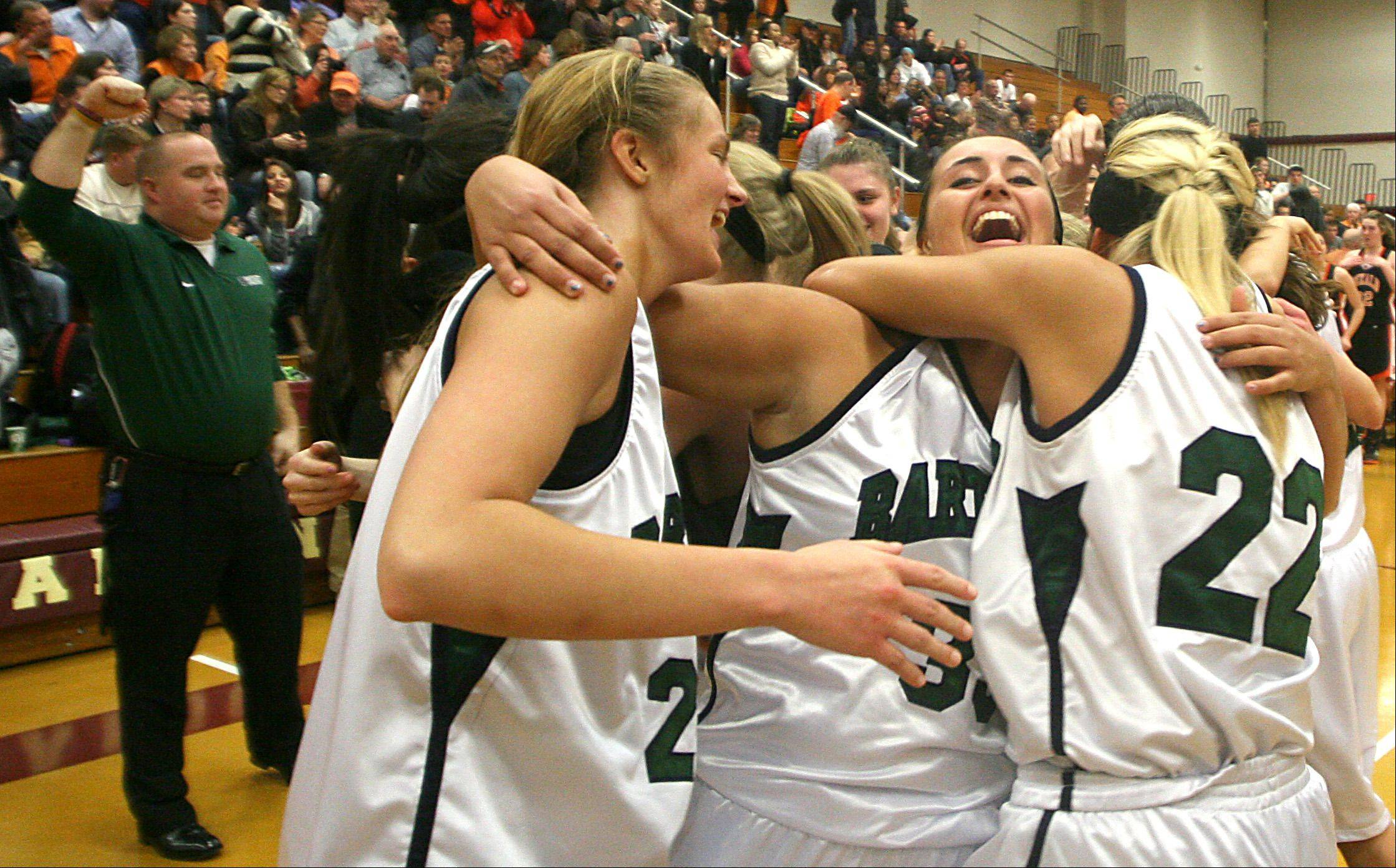 From left, Bartlett players Kristin Conniff, Tracy Raggio, and Haley Videckis hug as they celebrate a supersectional win over DeKalb at Chesbrough Field House in Elgin on Monday night.