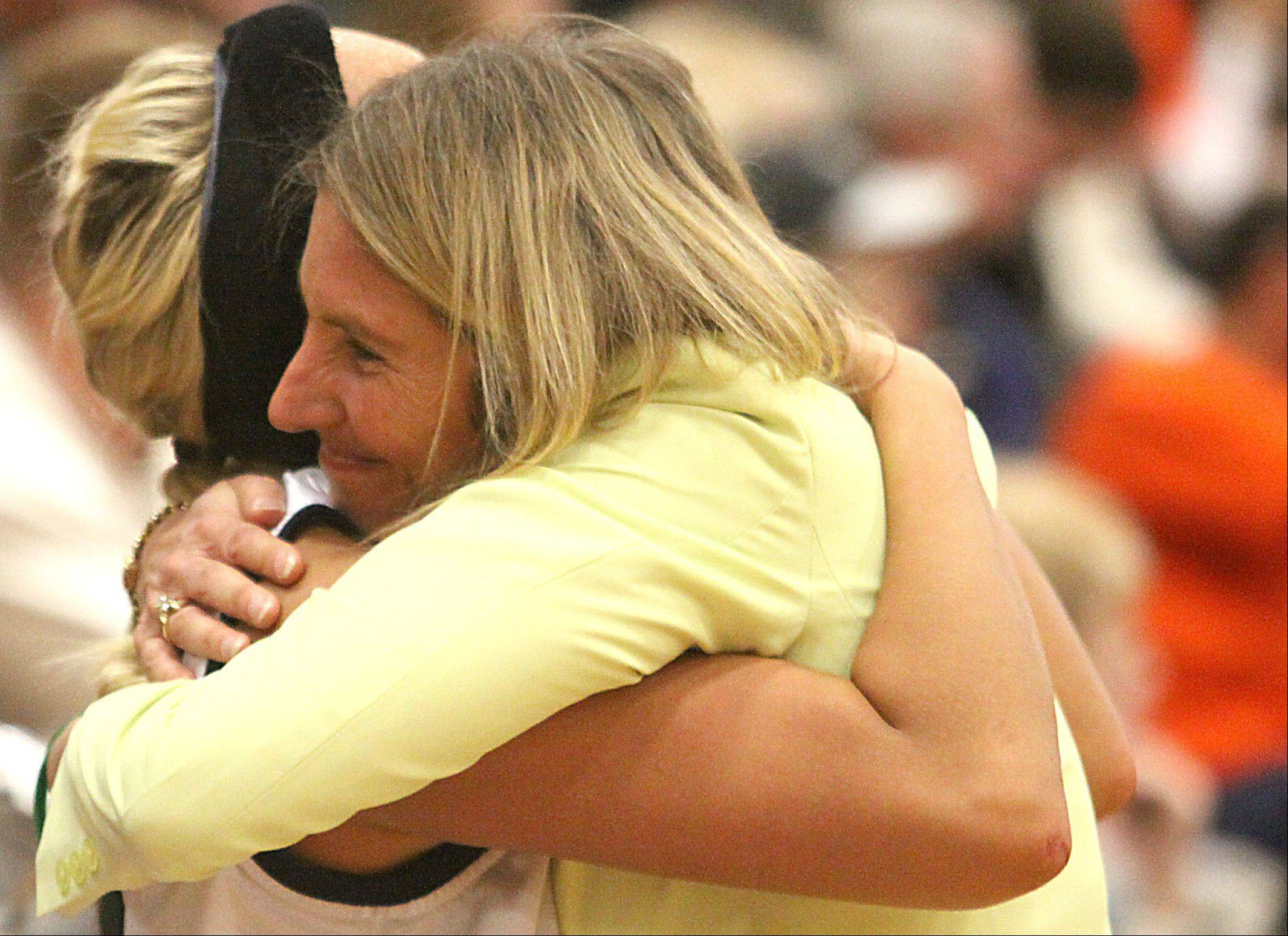 Bartlett girls basketball coach Denise Sarna, right, and player Haley Videckis embrace in celebration of a supersectional victory over DeKalb at Chesbrough Field House in Elgin on Monday night.