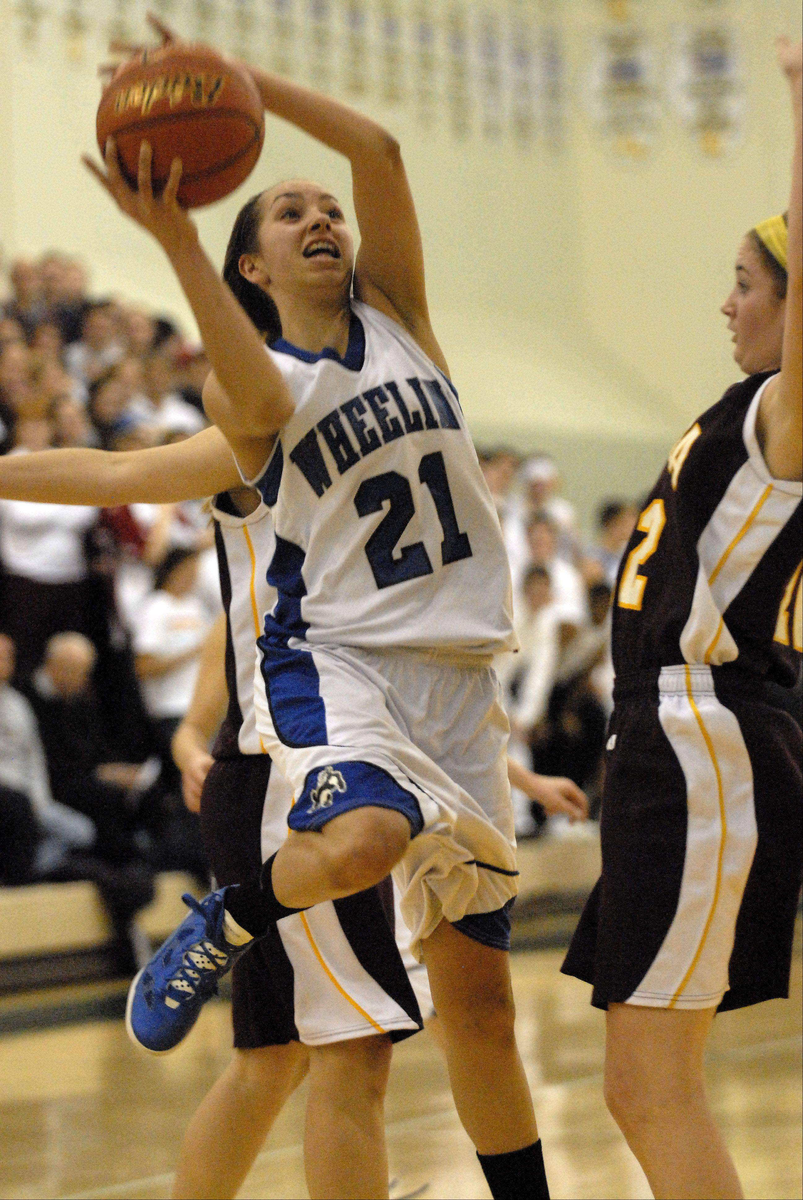 Wheeling's Deanna Kuzmanic puts up a shot against Loyola's Maggie Nick.