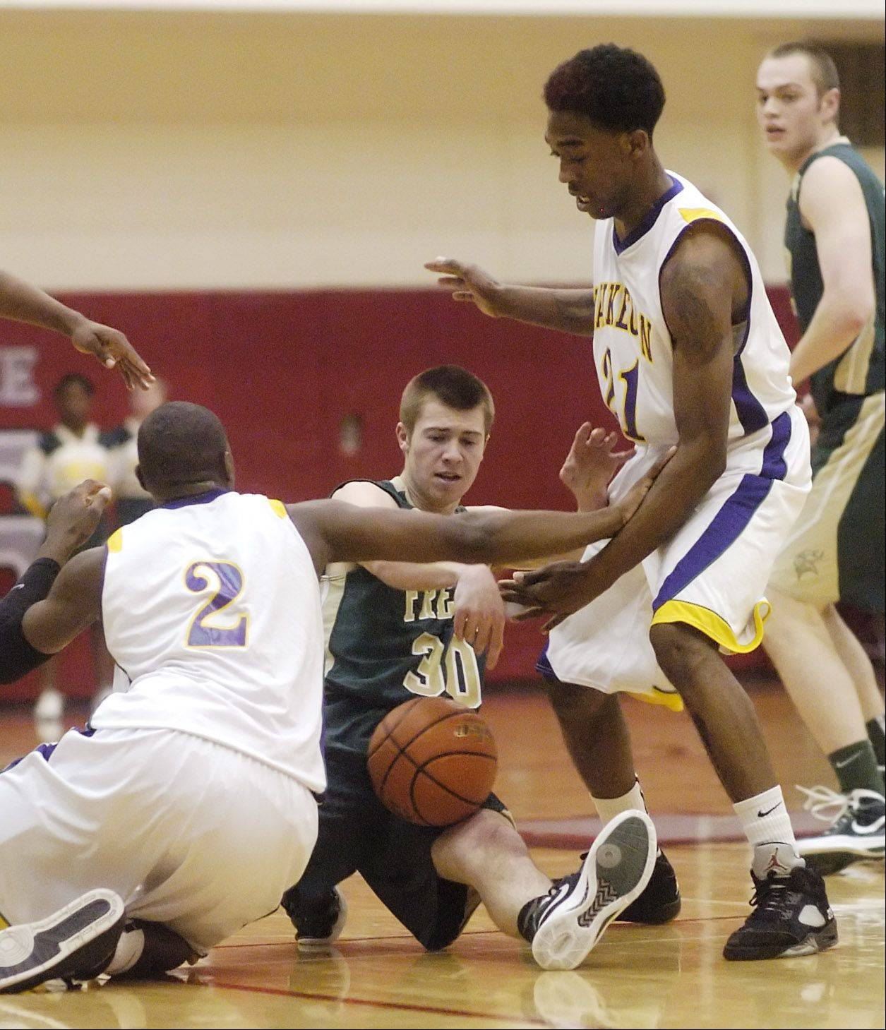 Waukegan defenders Akeem Springs, left, and DeVonte Taylor, right, try to force a turnover on Fremd's Matt Wisniewski.