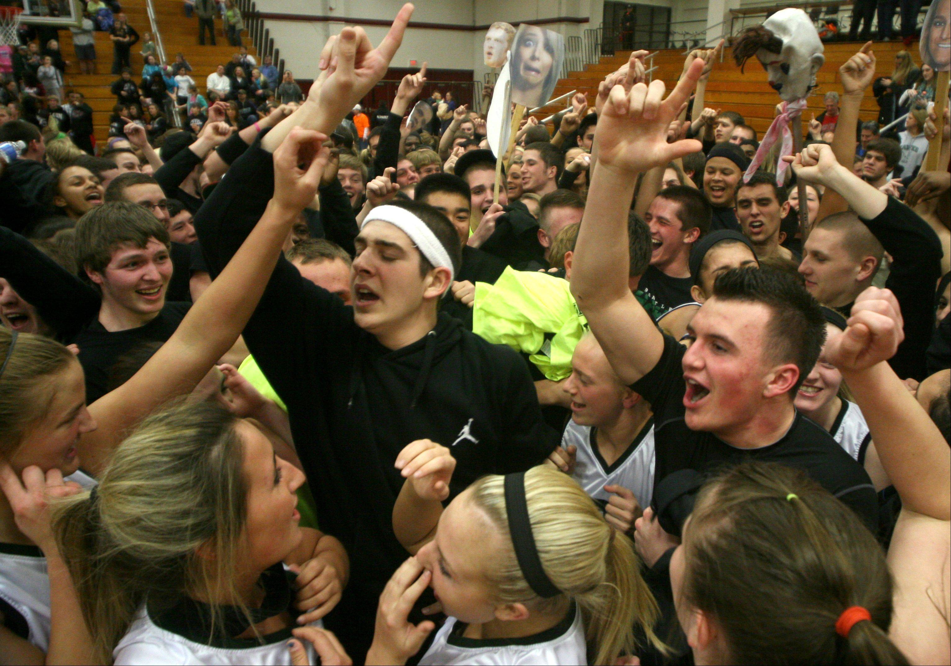 Bartlett fans swarm the girls basketball team and coaching staff as they celebrate a supersectional victory over DeKalb at Chesbrough Field House in Elgin on Monday night.