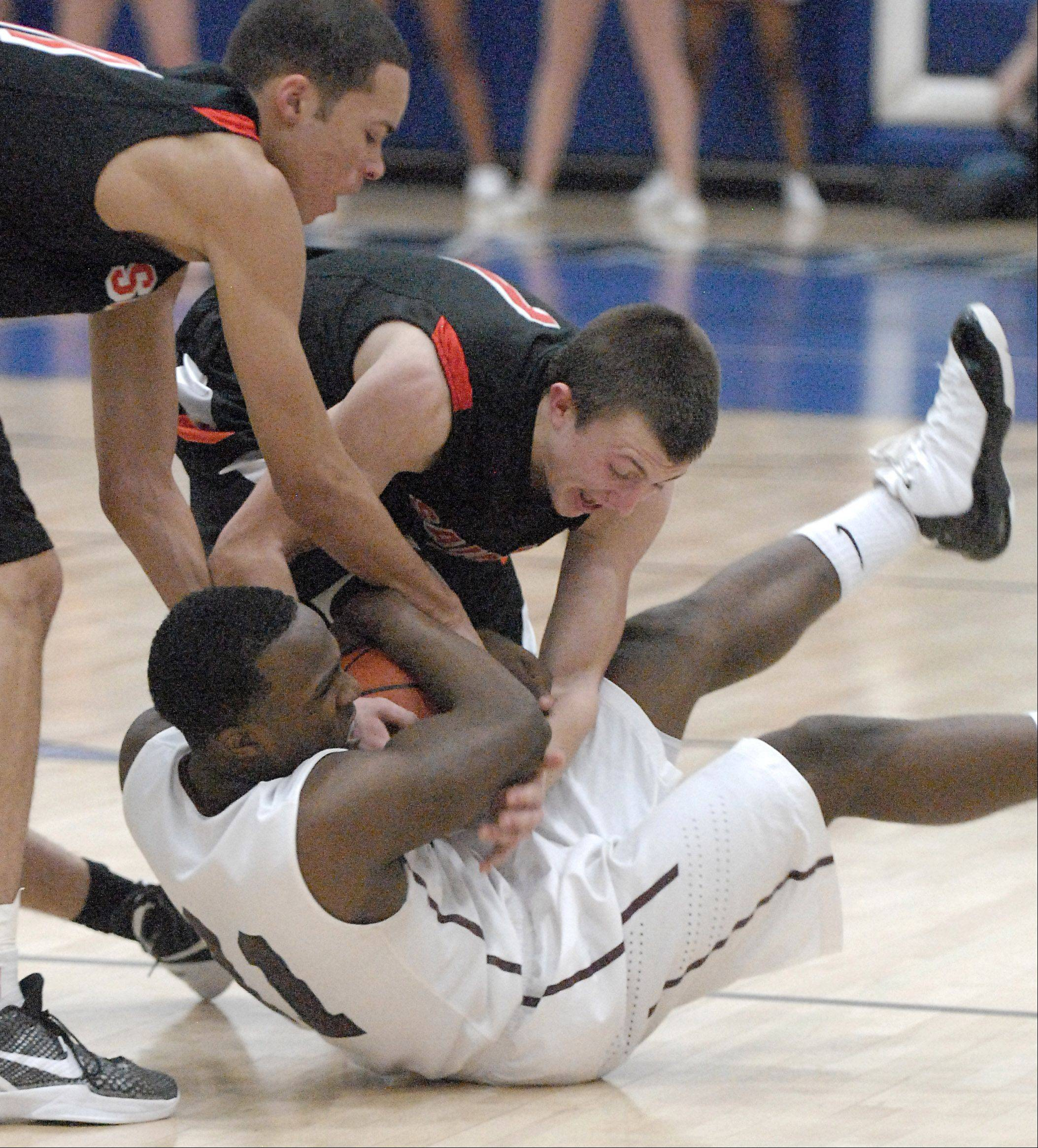 St. Charles East's Kendall Stephens and Charlie Fisher rush to wrestle a loose ball from Elgin's Dennis Moore in the fourth quarter.