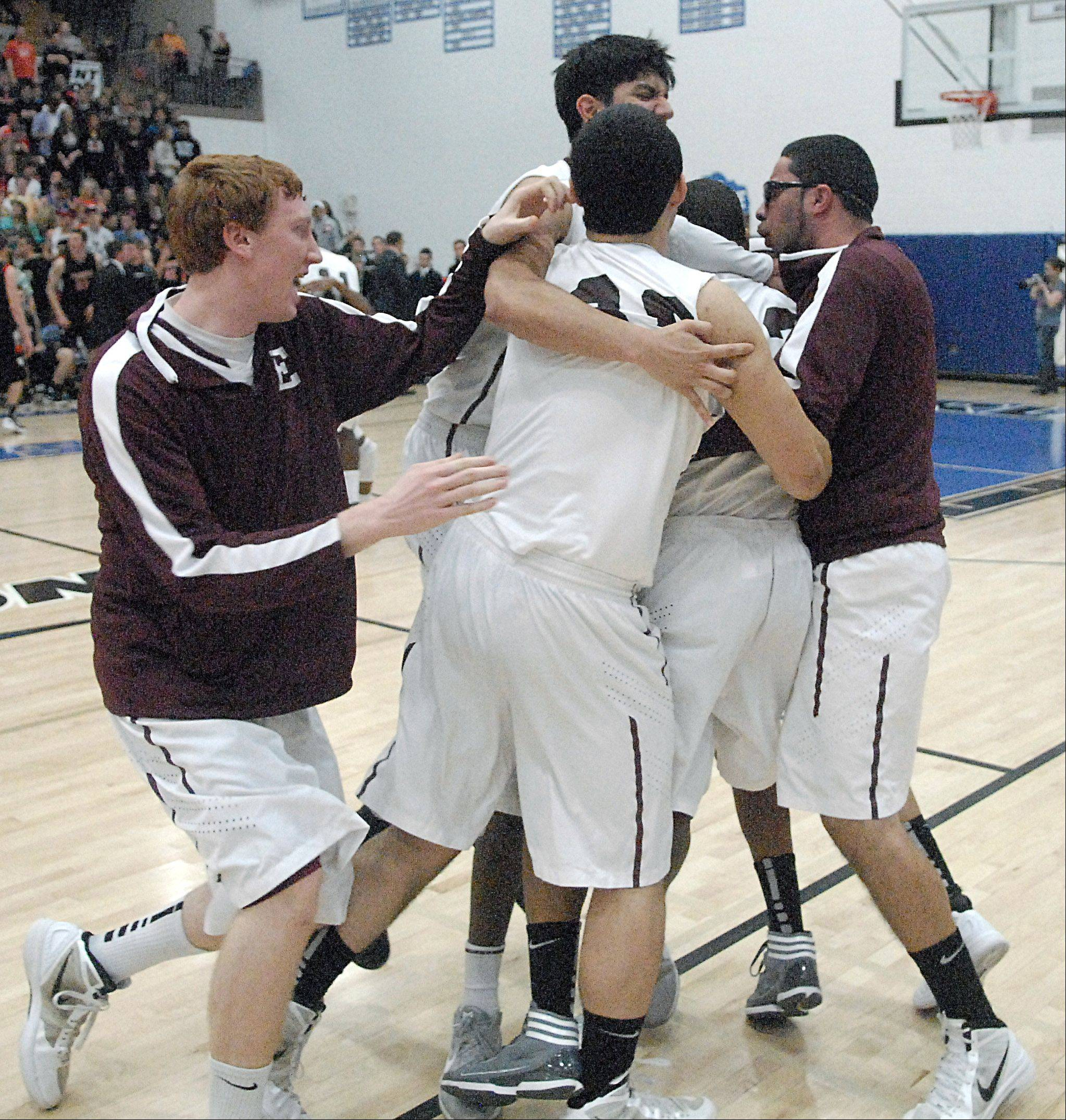 Elgin's Arie Williams is mobbed on the floor after the Maroons' win.