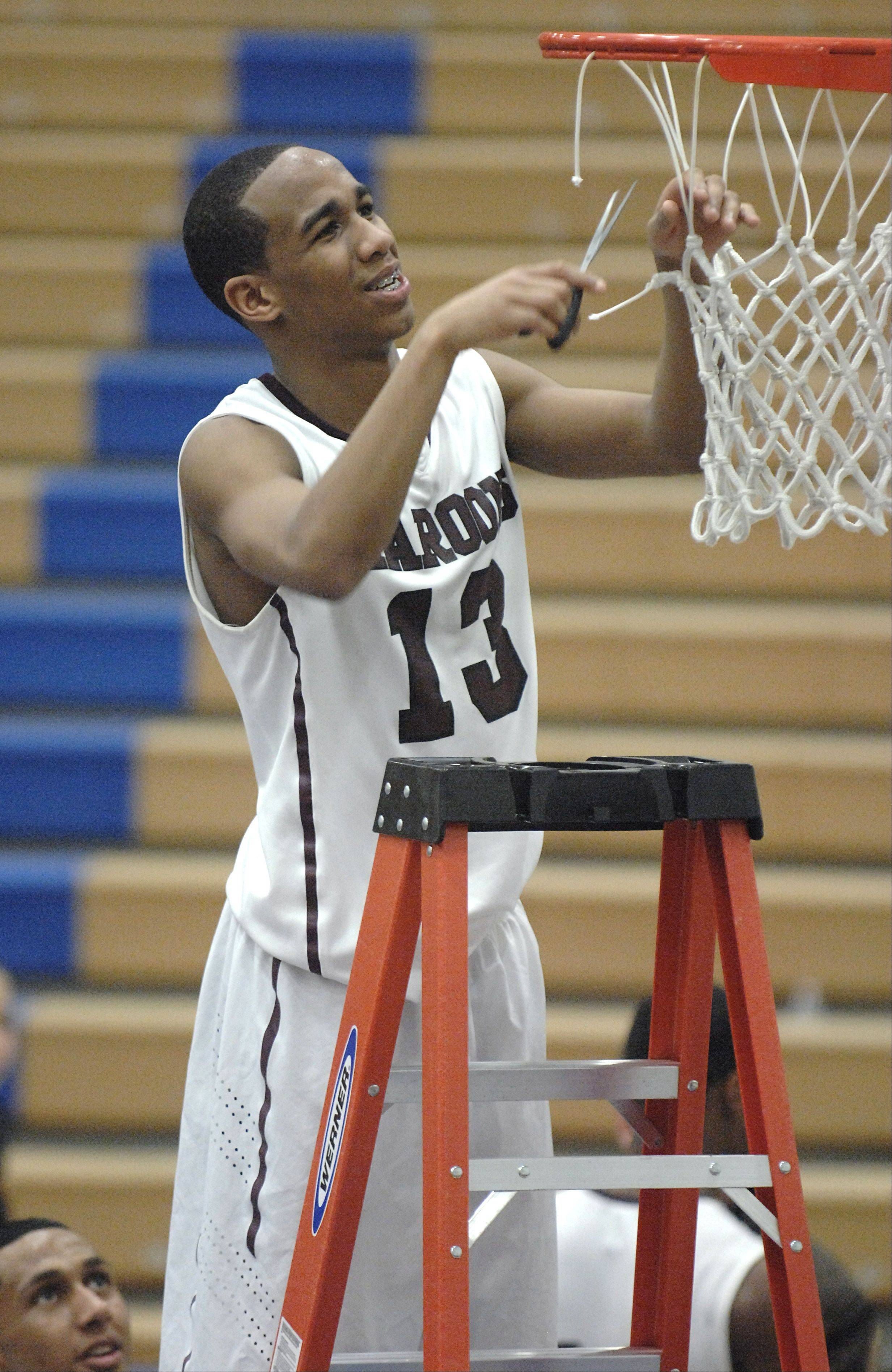 Elgin's Cortez Scott approached the basket smiling the entire time as he cut down a piece of the net after their 4A regional championship win.