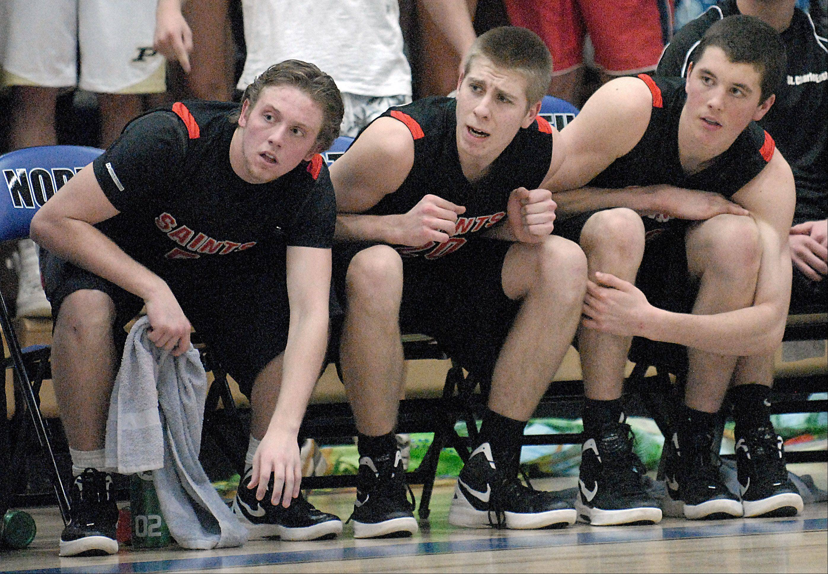 St. Charles East's Dom Urso, Ben Skoog and David Mason lean over in hopes of Elgin missing a free throw in the final seconds.