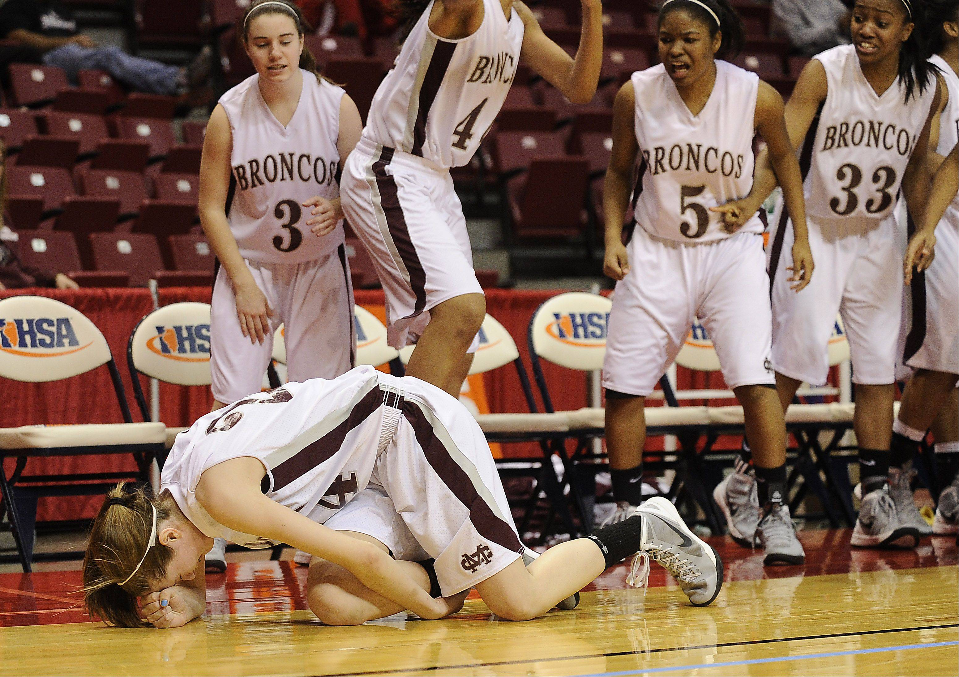 Montini's Kateri Stone goes down after shooting a three-pointer late in the second half against Hillcrest in the 2012 IHSA Class 3A Girls Basketball Tournament in Normal, Illinois on Friday.
