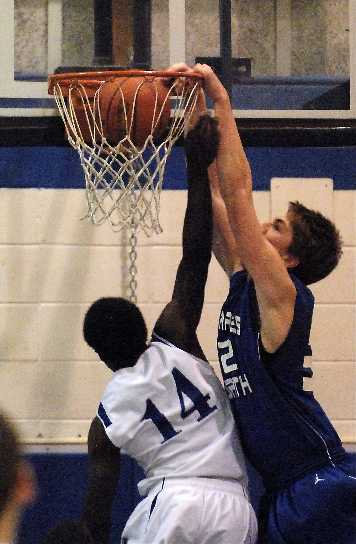 St. Charles North's Kyle Nelson dunks over Larkin's Brent Cooks during Thursday's game at Larkin High School in Elgin.