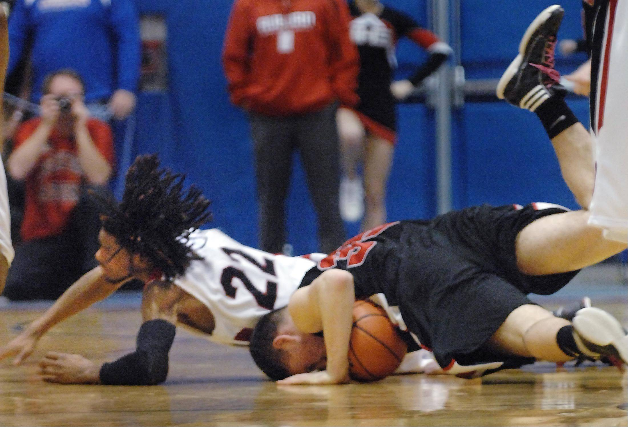 Huntley's Justin Frederick gets his head slammed to the floor as Rockford Auburn's LaMark Foote falls on him as they chase a loose ball.