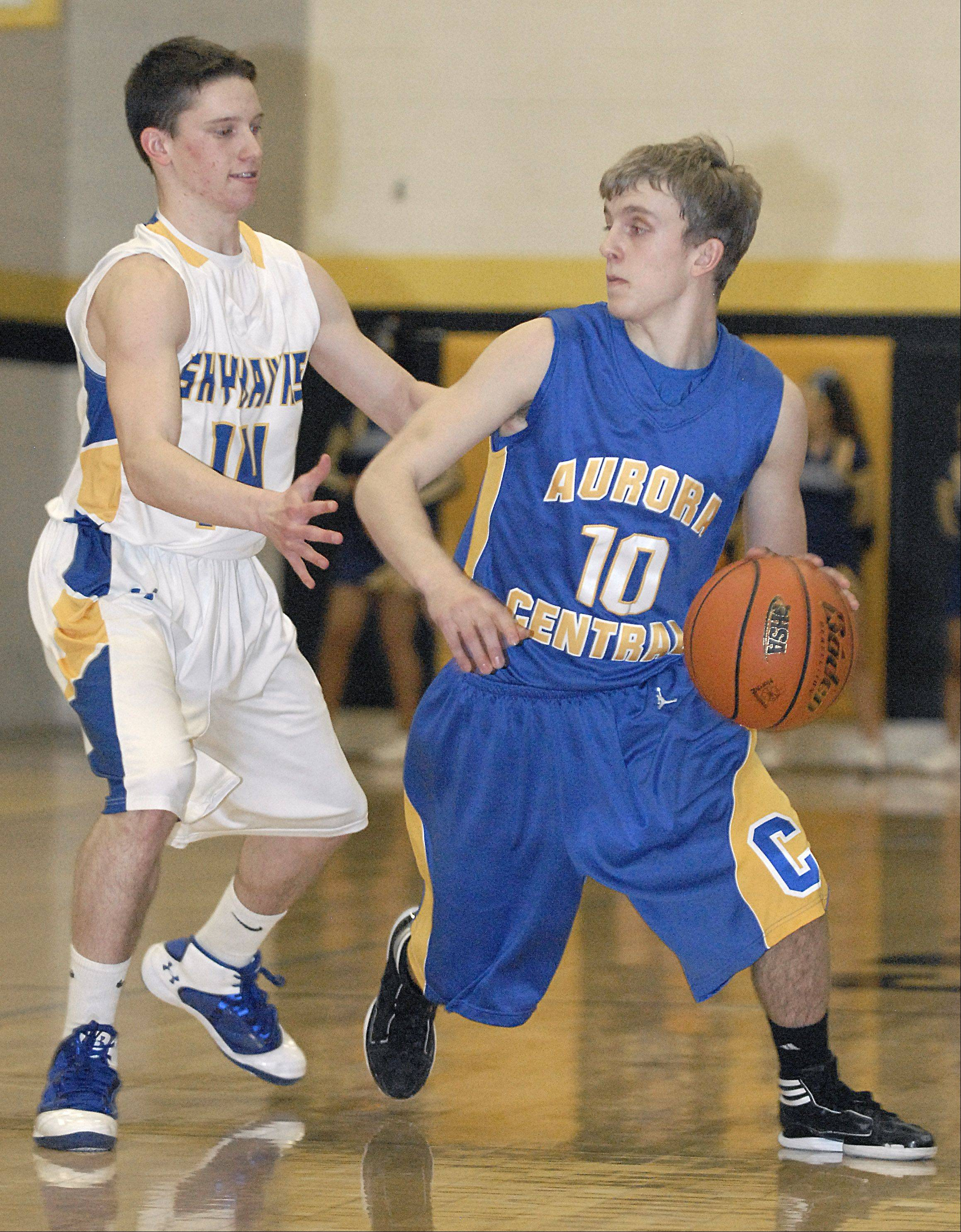 Aurora Central Catholic's Shawn Soris looks to pass around Johnsburg's Brett Toussaint in the first quarter of the sectional game on Wednesday, March 7.
