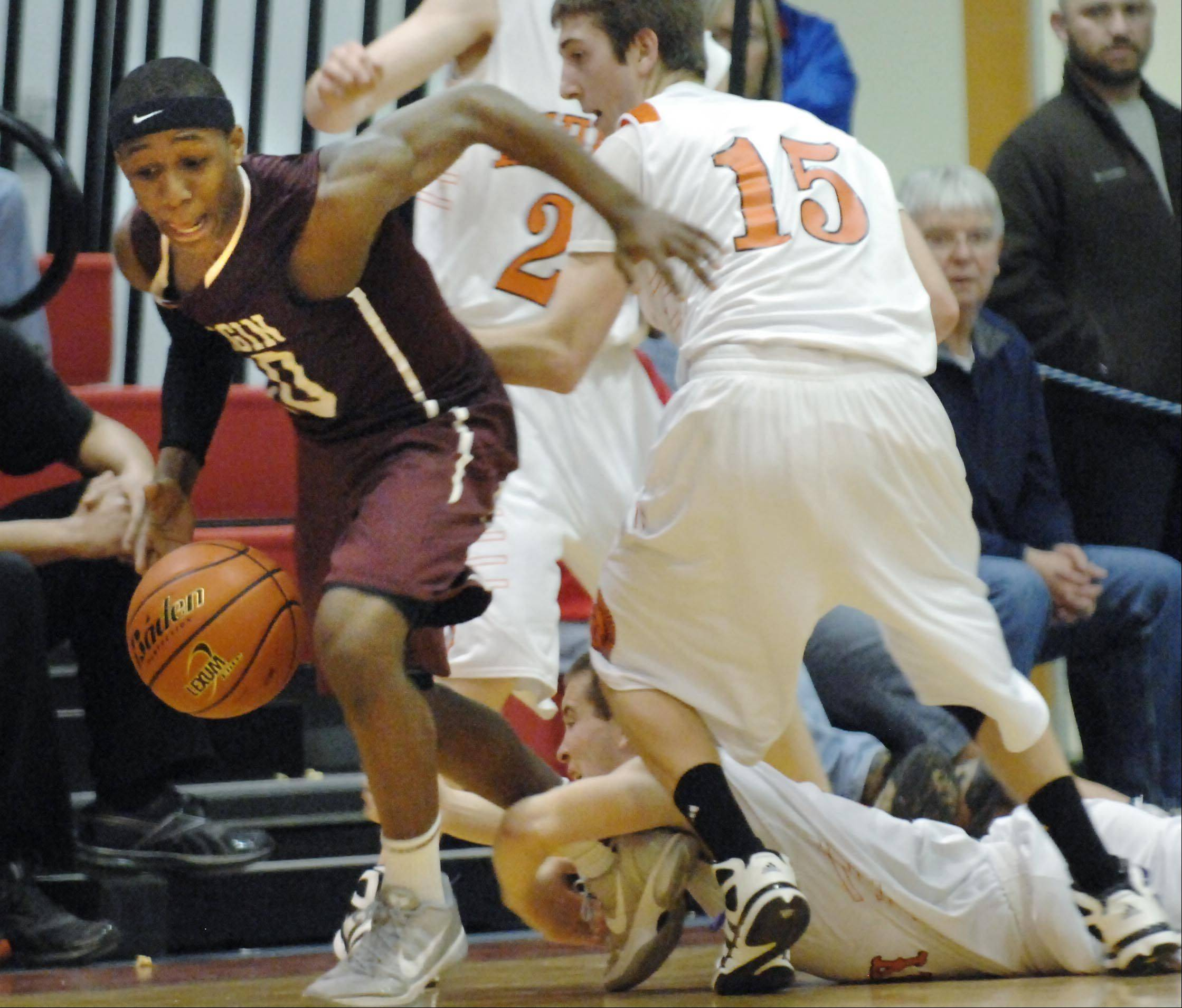 McHenry's Kyle Clark grabs the ankle of Elgin's Arie Williams as he splits the defense of McHenry's Jeff Nicholls and Danny Glick Wednesday in the Class 4A Dundee-Crown sectional semifinal game in Carpentersville. A foul was called on Clark.