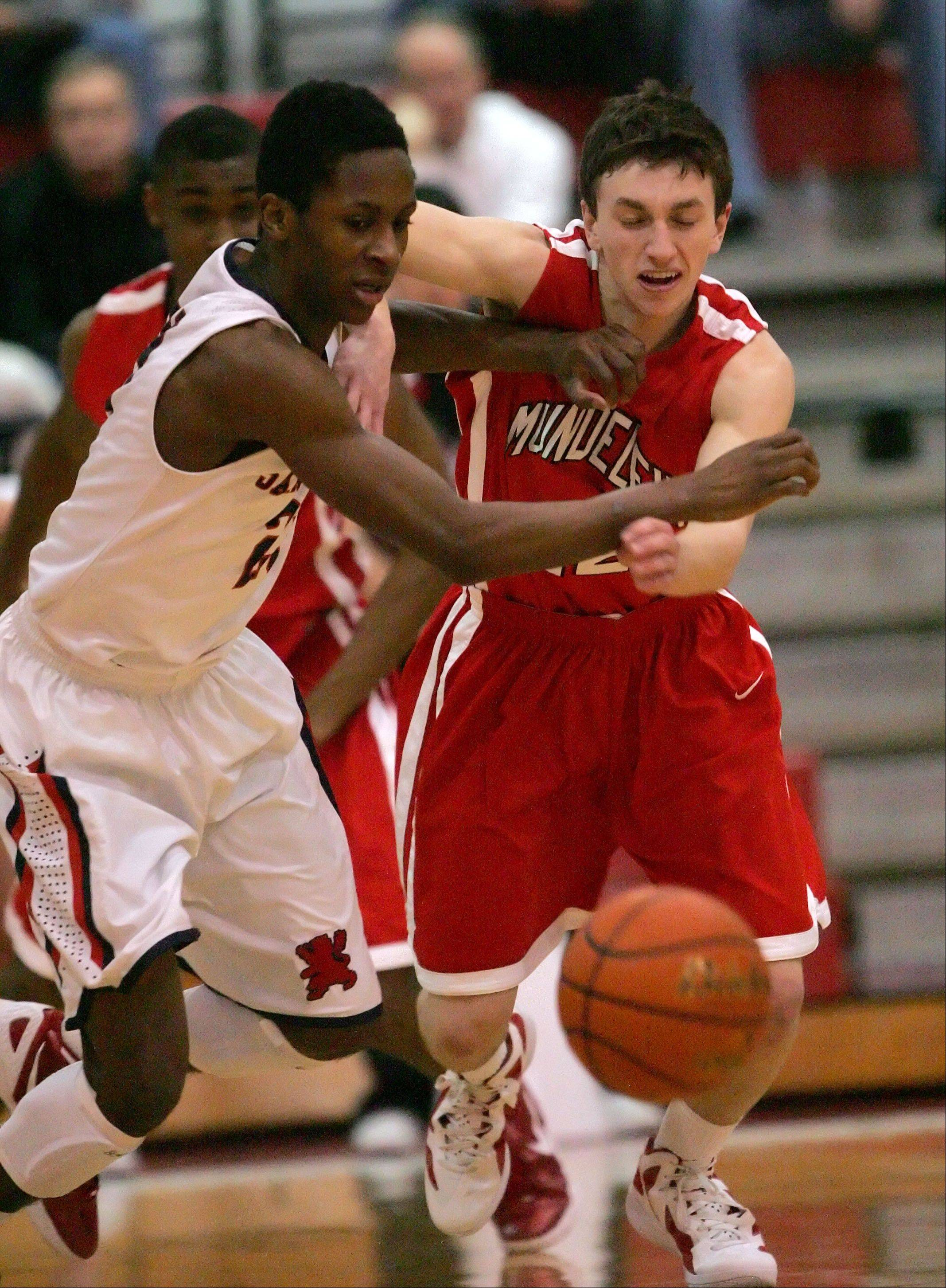St. Viator's Ore Arogundale, left, and Mundelein's Quinn Pokora battle for a loose ball.