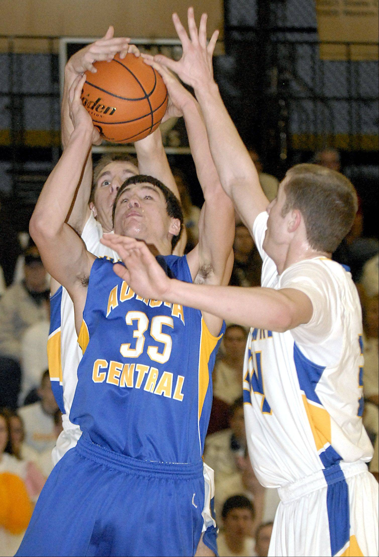 Aurora Central Catholic's Phil Schuetz attempts a shot while swarmed by Johnsburg's Mike Ward and TJ Sigmund in the first quarter .