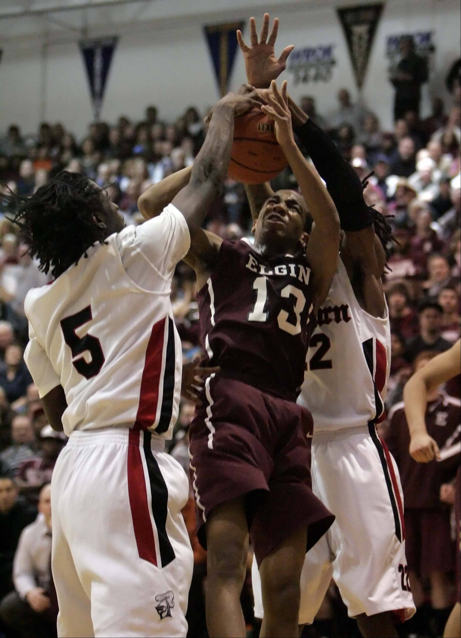 Elgin wing Cortez Scott is fouled on his way to the hoop by Auburn guard Elijah Smith and Auburn guard LaMark Foote .