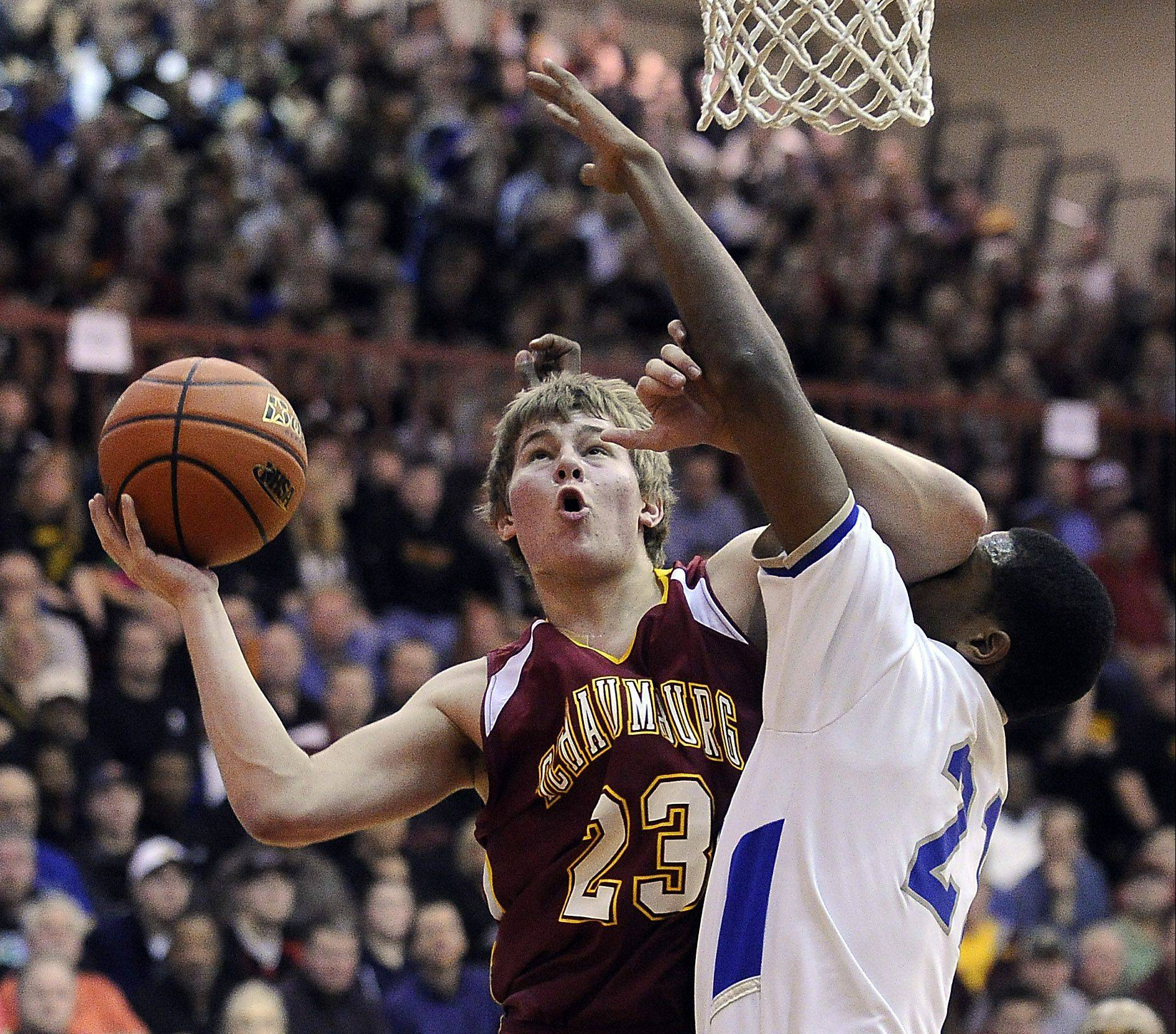 Schaumburg's Kyle Bolger powers his way to the basket with Proviso East's Sterling Brown defending in sectional final action at Schaumburg on Friday.