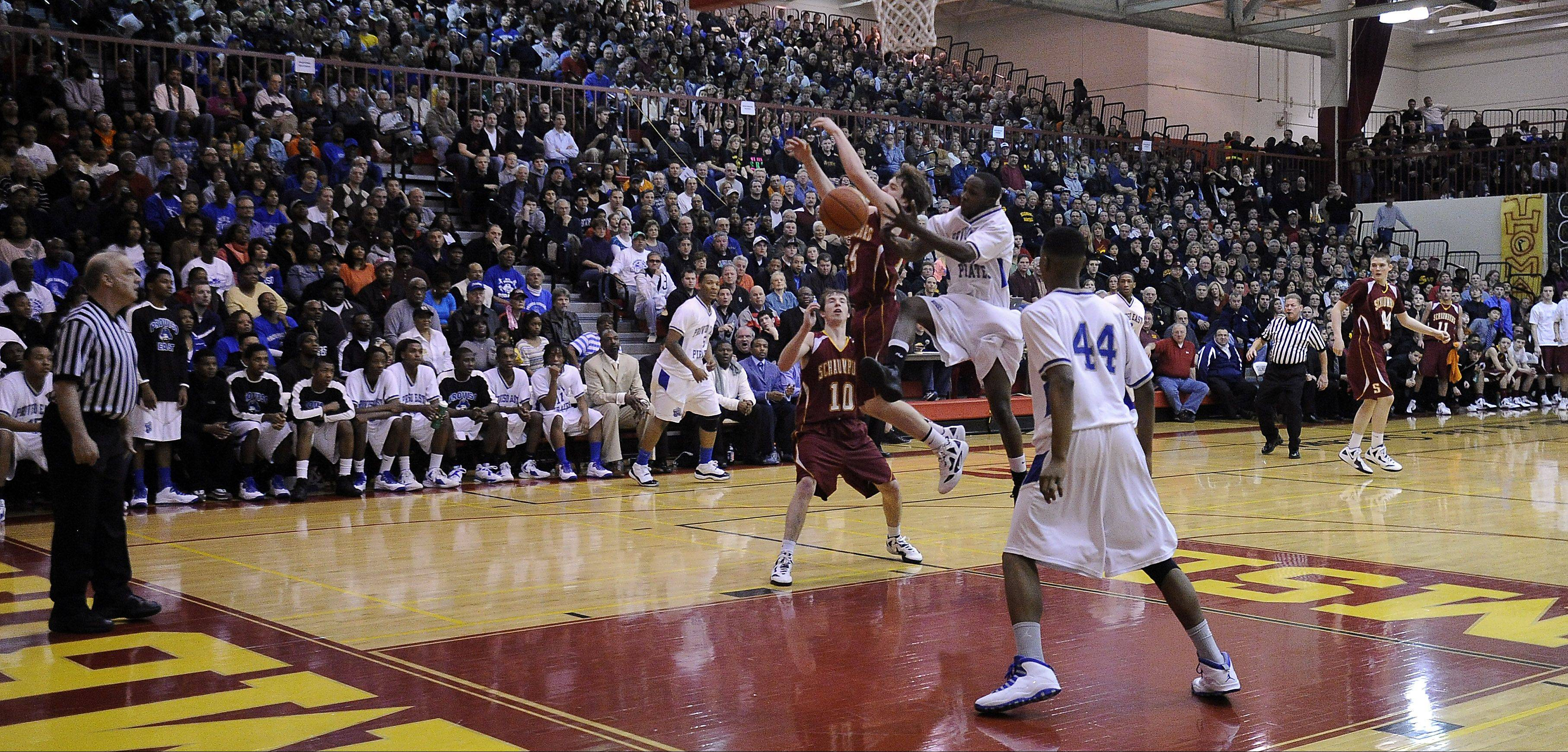 It's a battle in the paint as Schaumburg and Proviso East fight for a rebound before a packed house at Schaumburg on Friday.