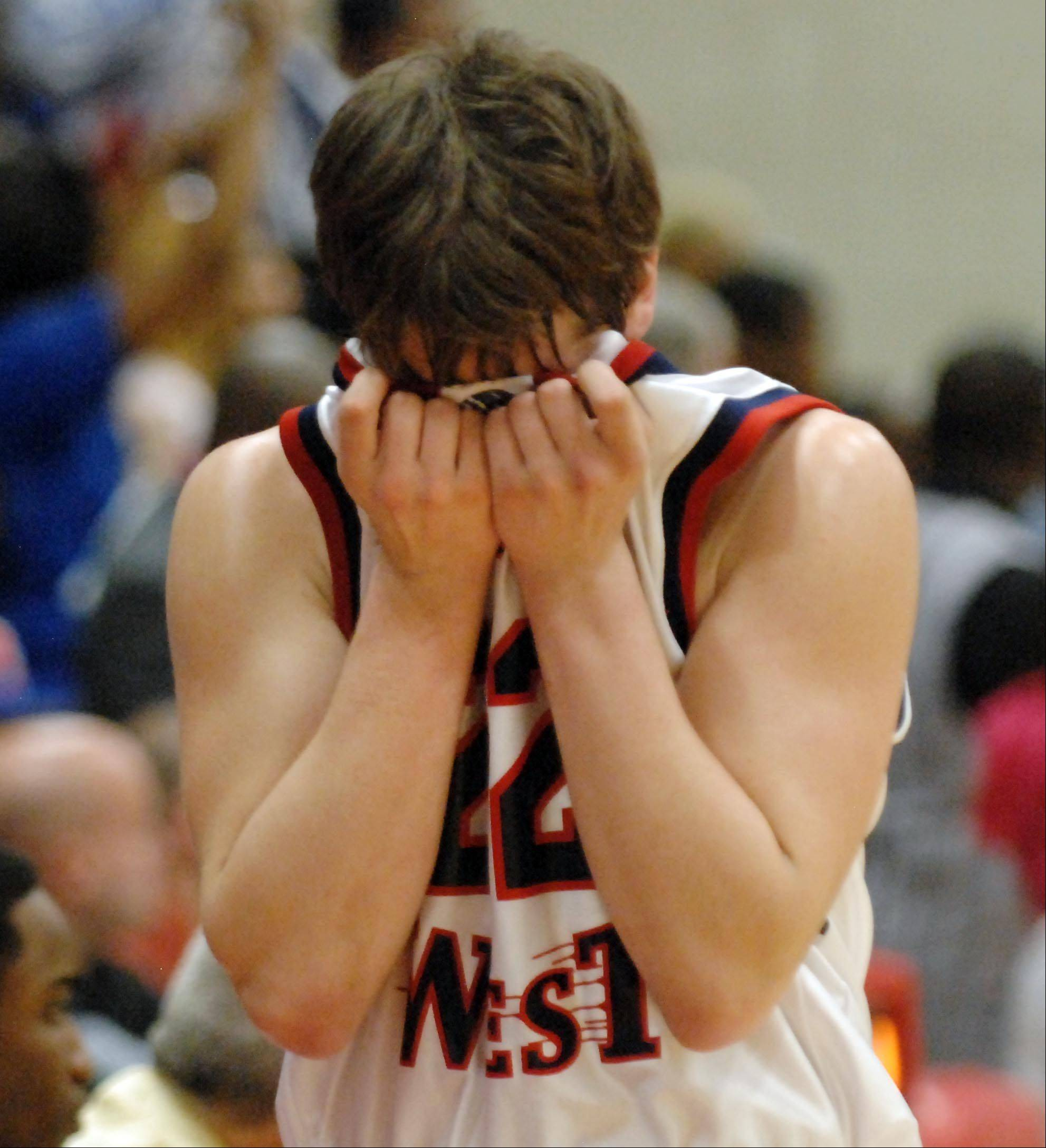 West Aurora's Brandon Gossett covers his face as he leaves the game with seconds left against Proviso East in Tuesday's Hinsdale Central supersectional game.