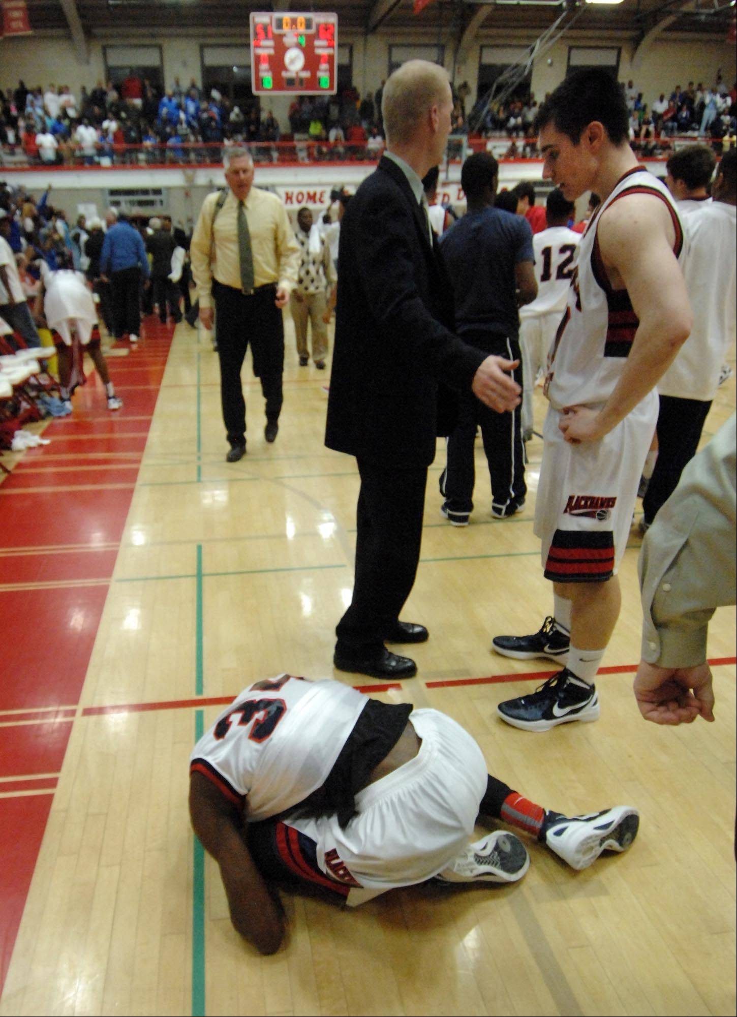 West Aurora's Juwan Starks curls up in a heap on the floor after losing to Proviso East in Tuesday's Hinsdale Central supersectional game.