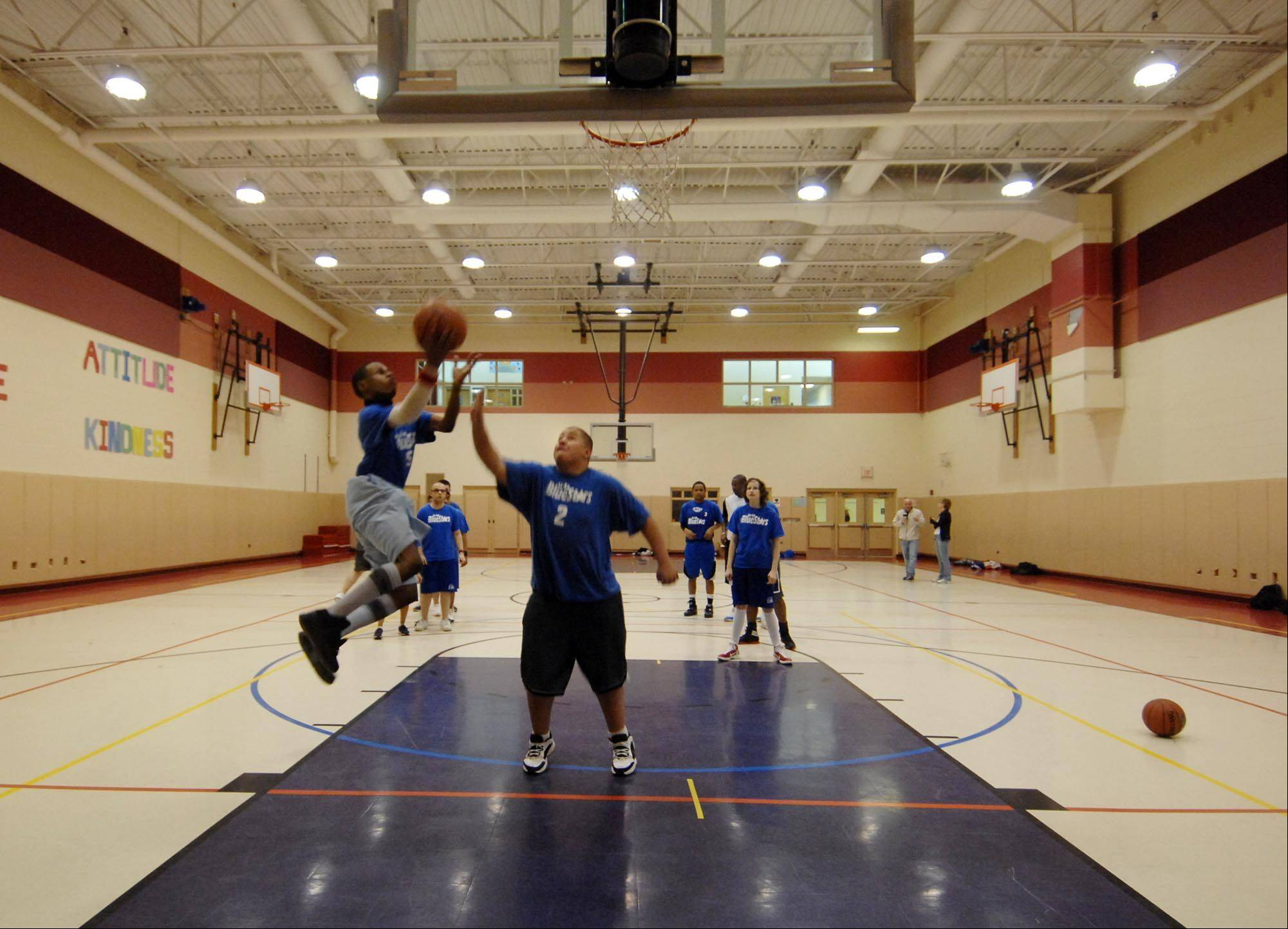 Eugene James lays up a basket as David Gomez defends during Elgin U46 Special Olympics BlueStars High School A team practice.