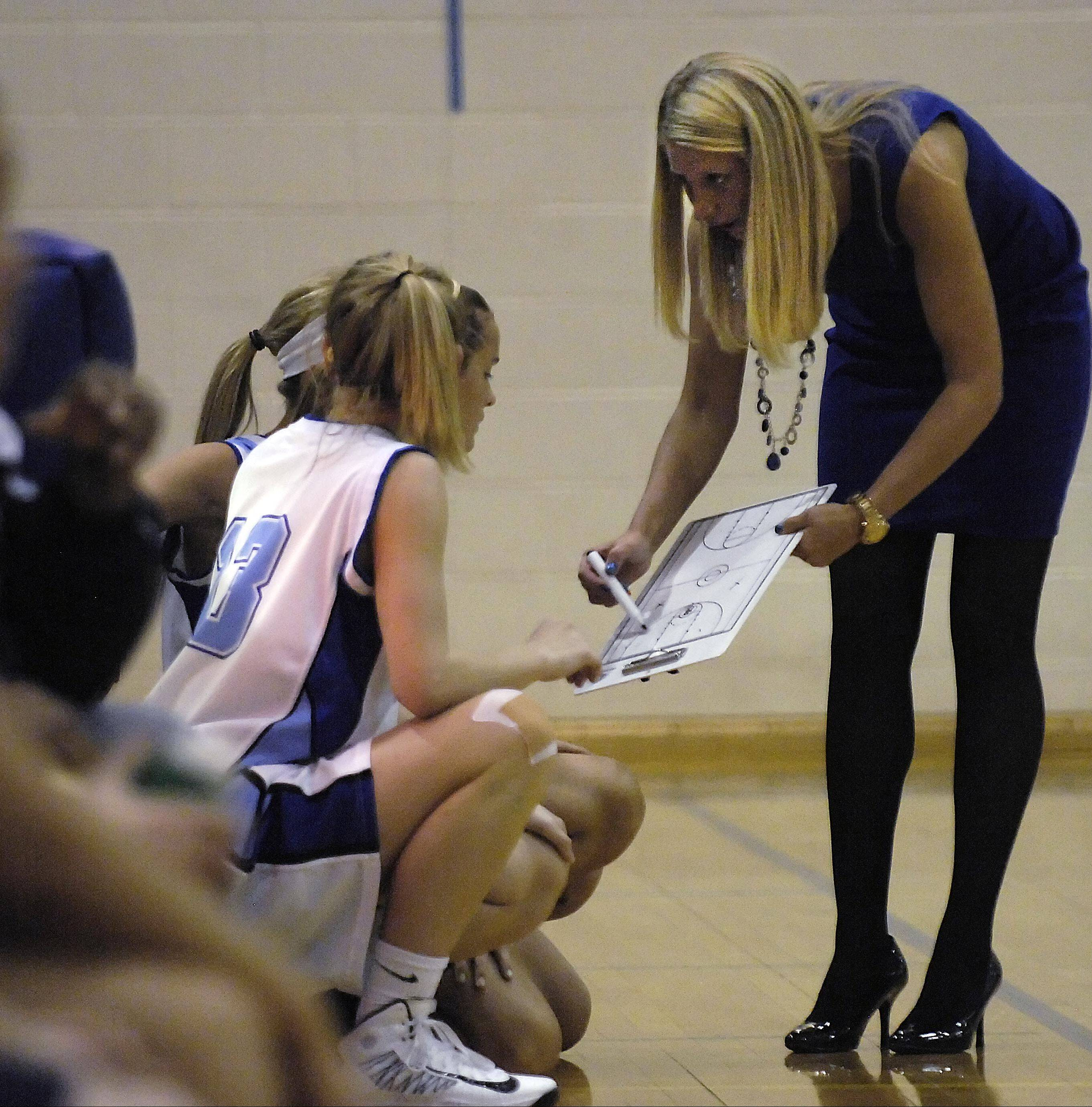 Rosary head coach Jessie Wilcox diagrams a play against IMSA Monday in Aurora. It was the first game for Wilcox, a Wisconsin native, with the Royals, and Rosary made it a good debut with a 58-23 victory.