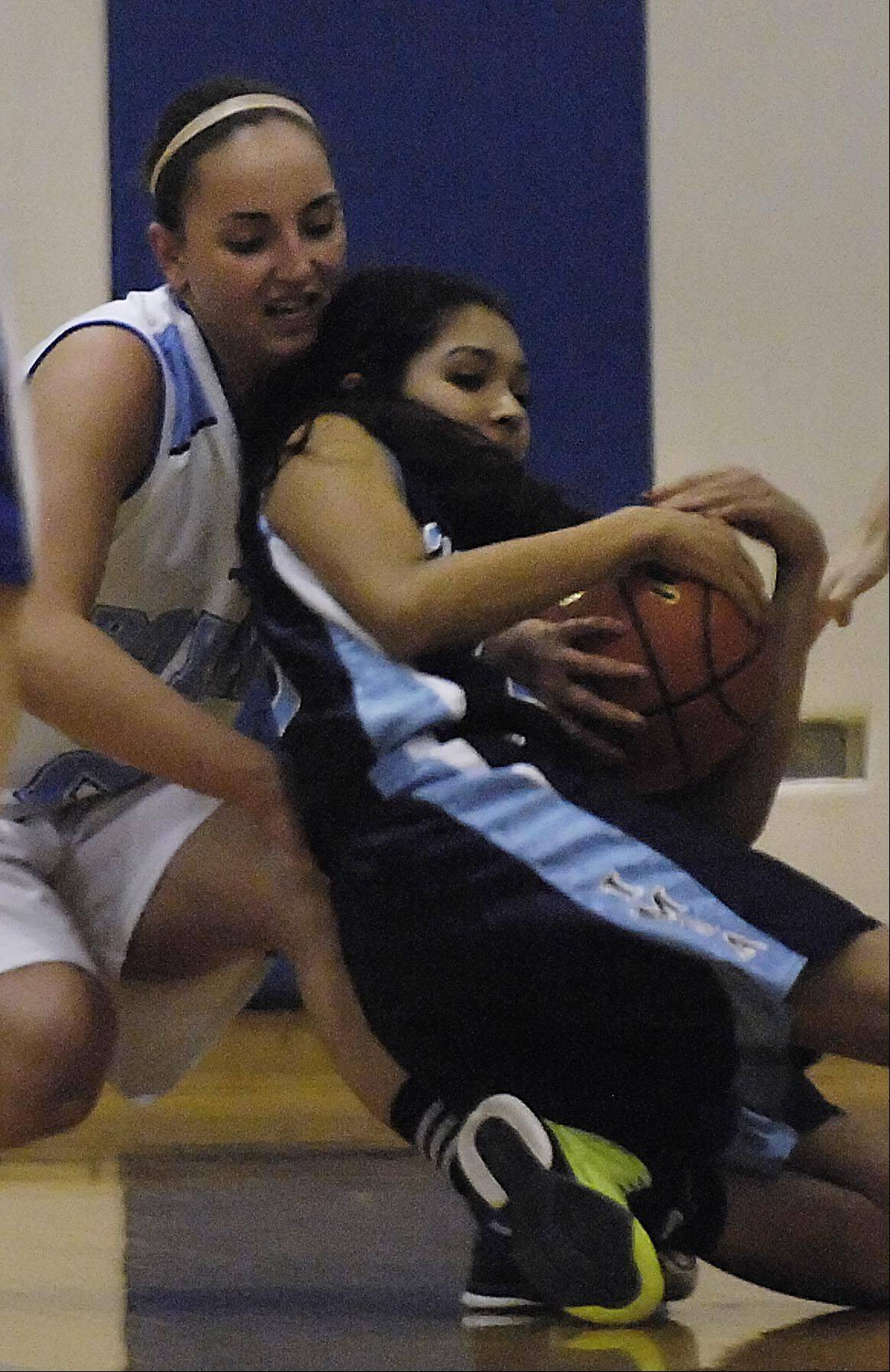 IMSA's Amy LeLa Torre falls to the floor as Rosary's Adrienne Winkel defends her Monday in Aurora.