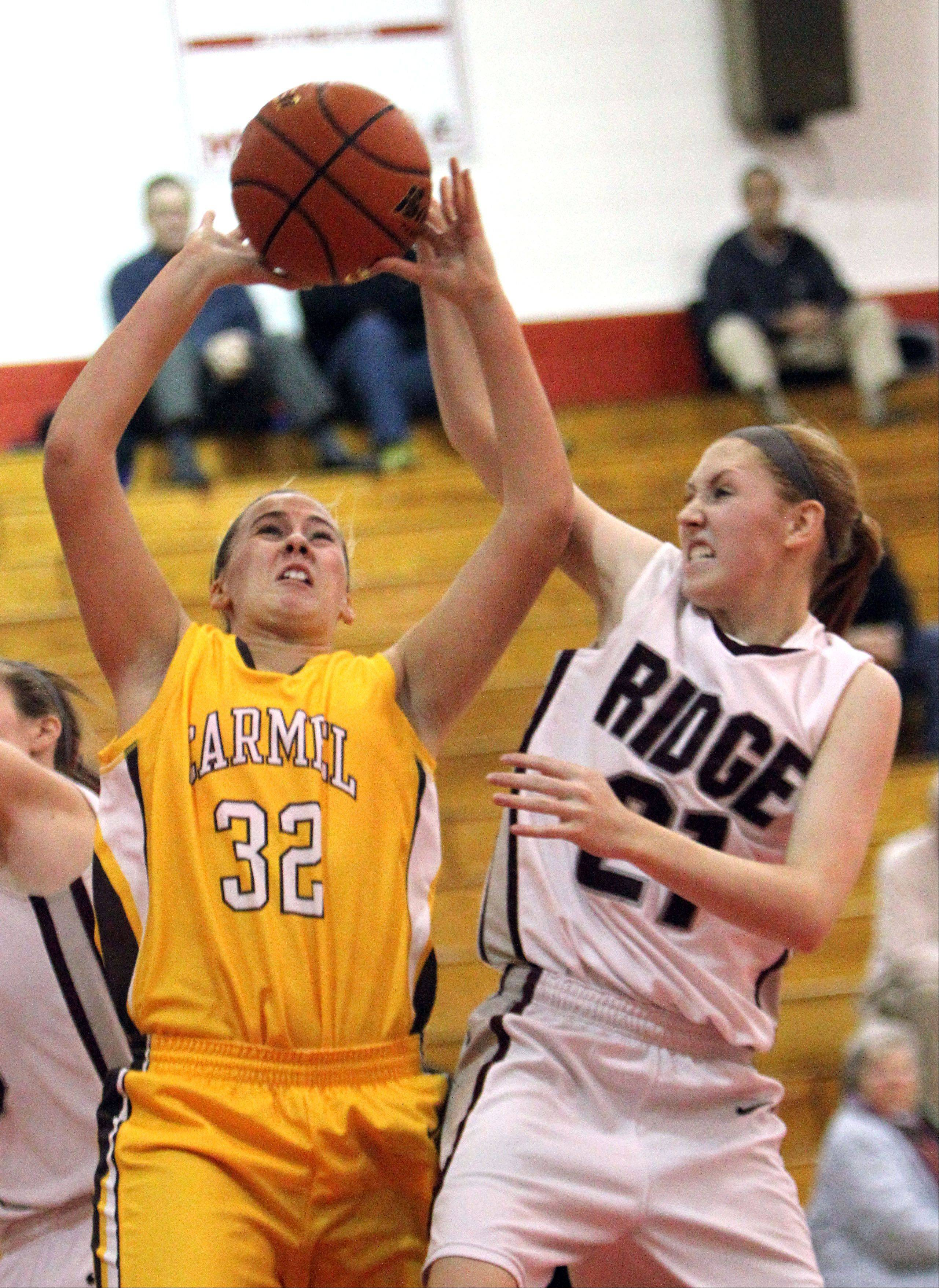 Carmel's Emma Rape, left, drives on Prairie Ridge's Kelly Klendworth at the Mundelein Turkey Tournament on Monday.